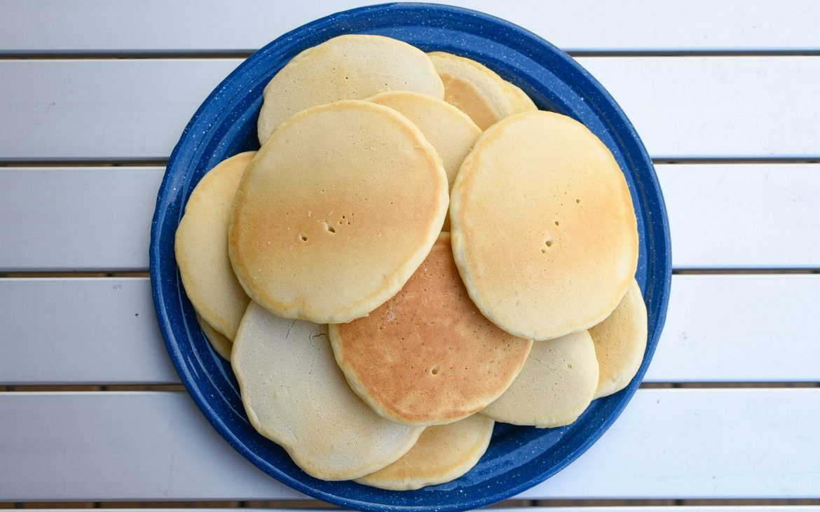 Many pancakes placed around a blue plate