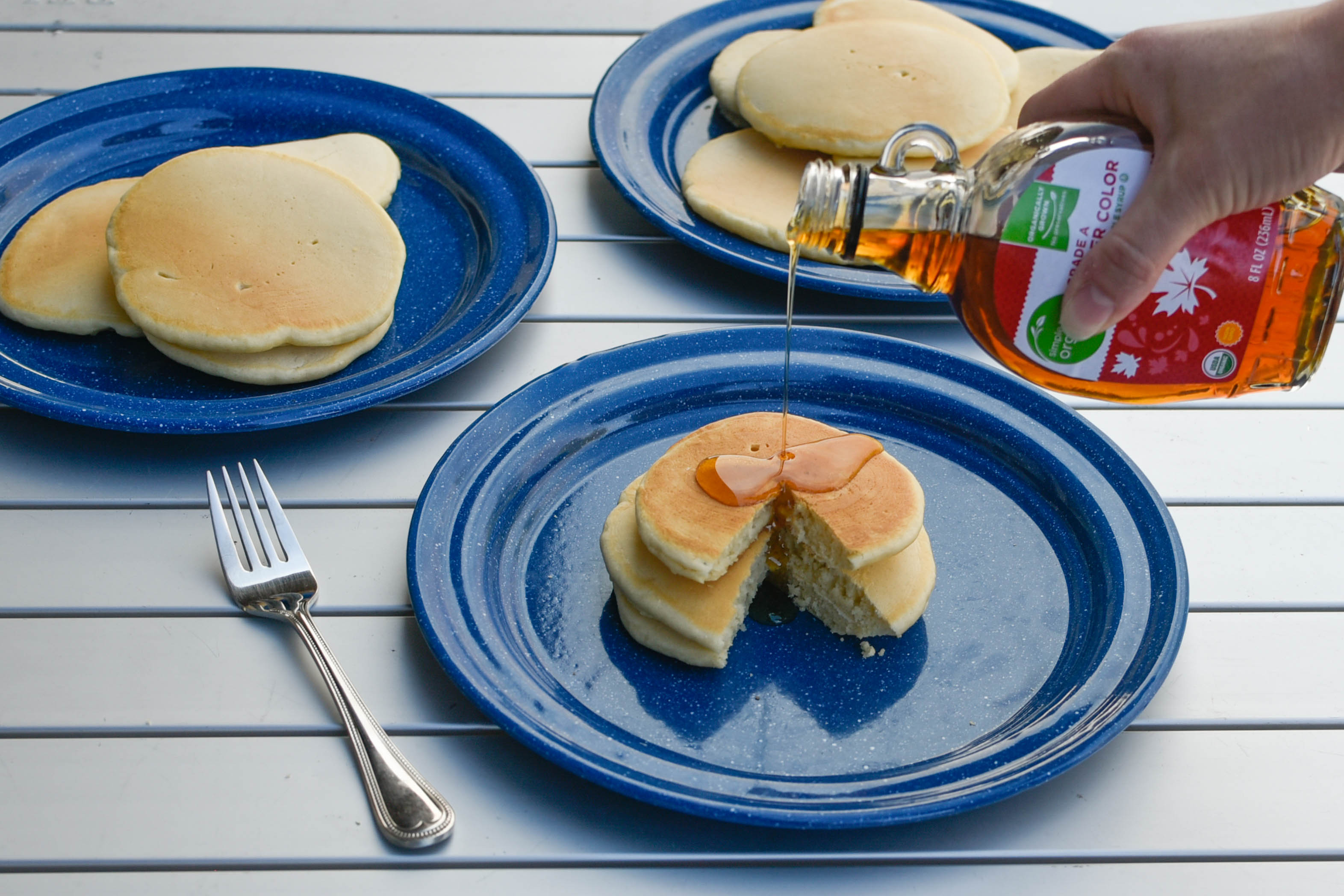 Blue plates with pancakes on them and syrup being poured on one plate