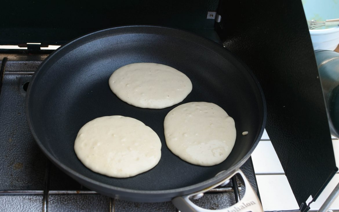 Three pancakes cooking on stove