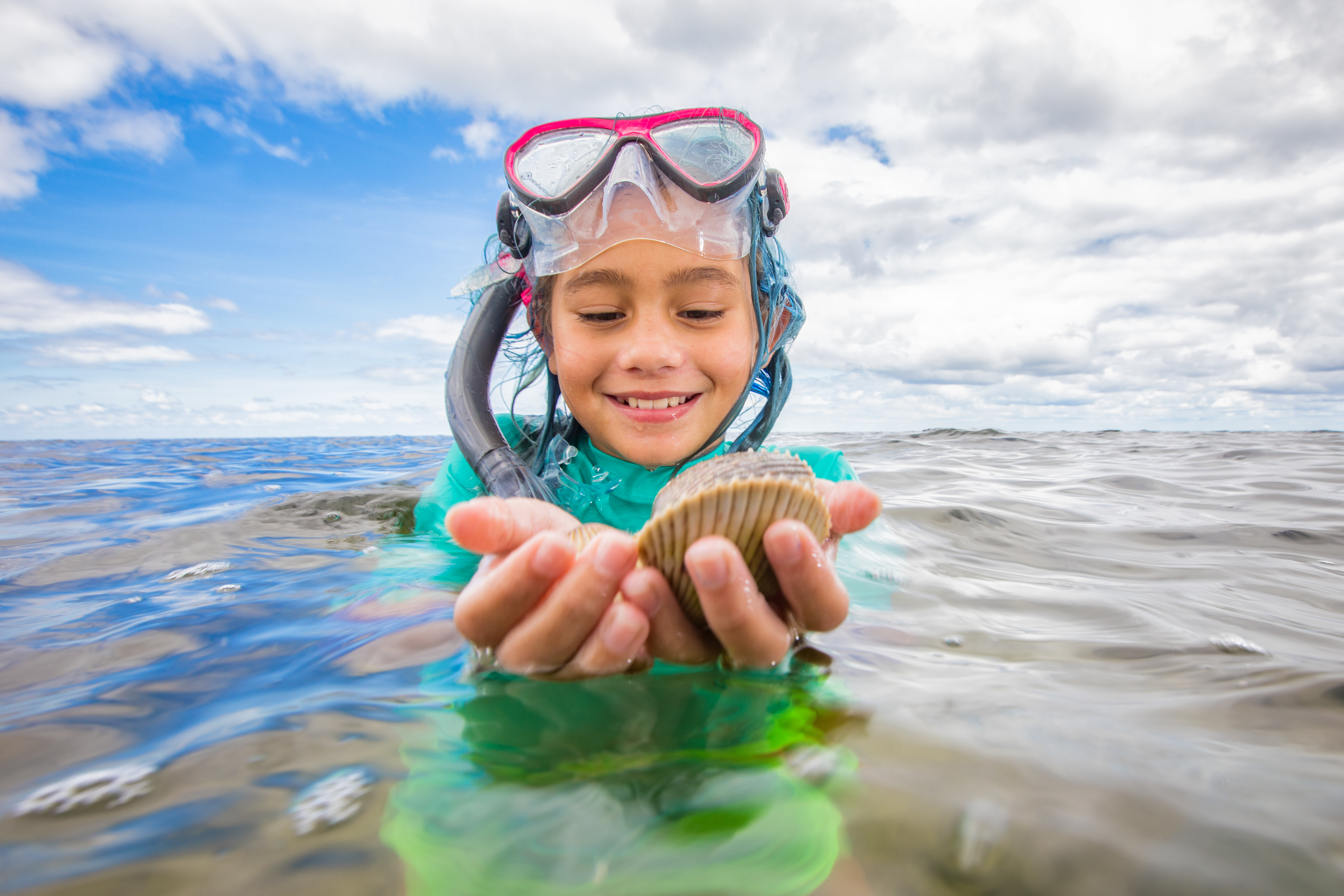 Girl treading water smiling and holding a scallop