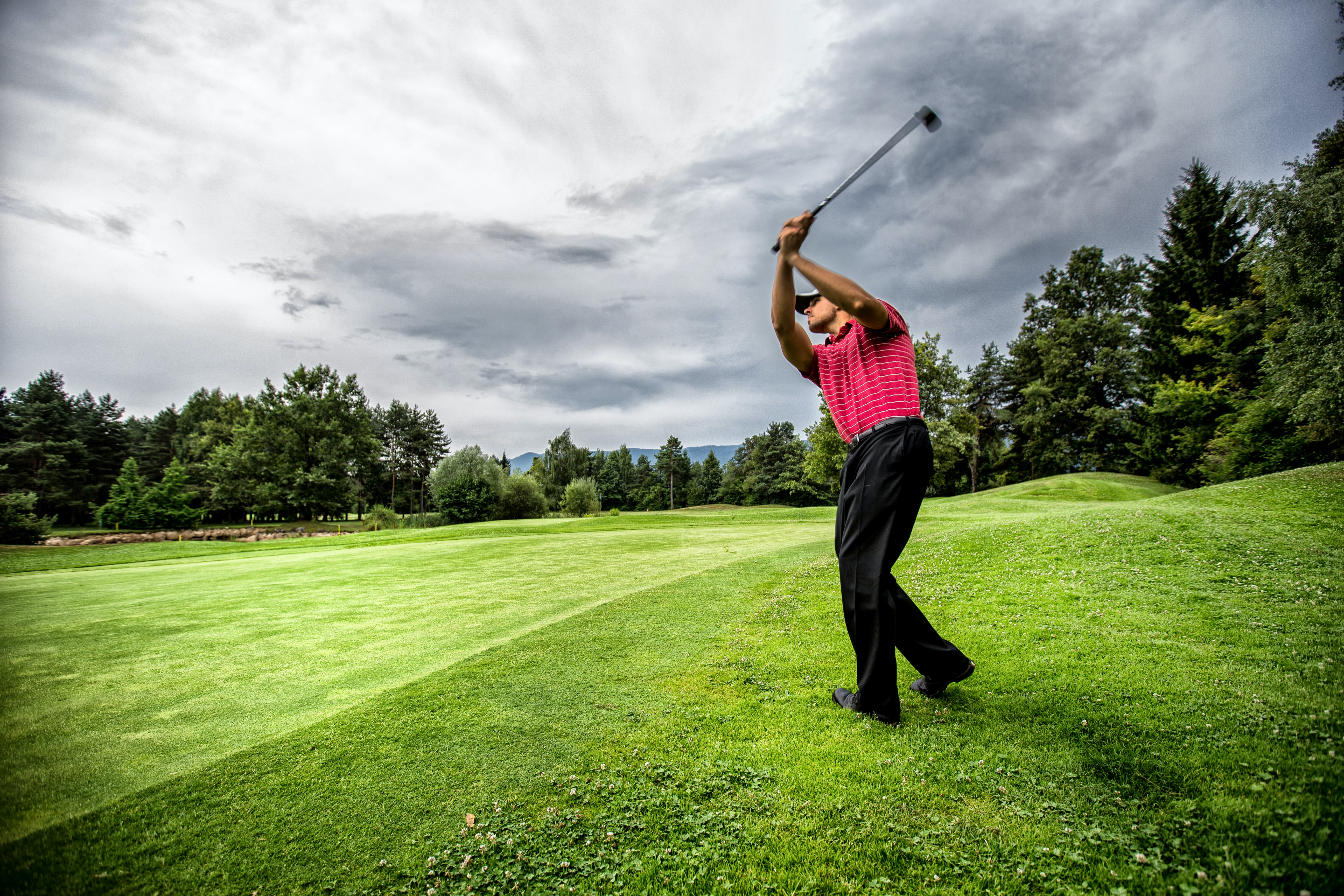A man completes the swing of a driver on a lush fairway.