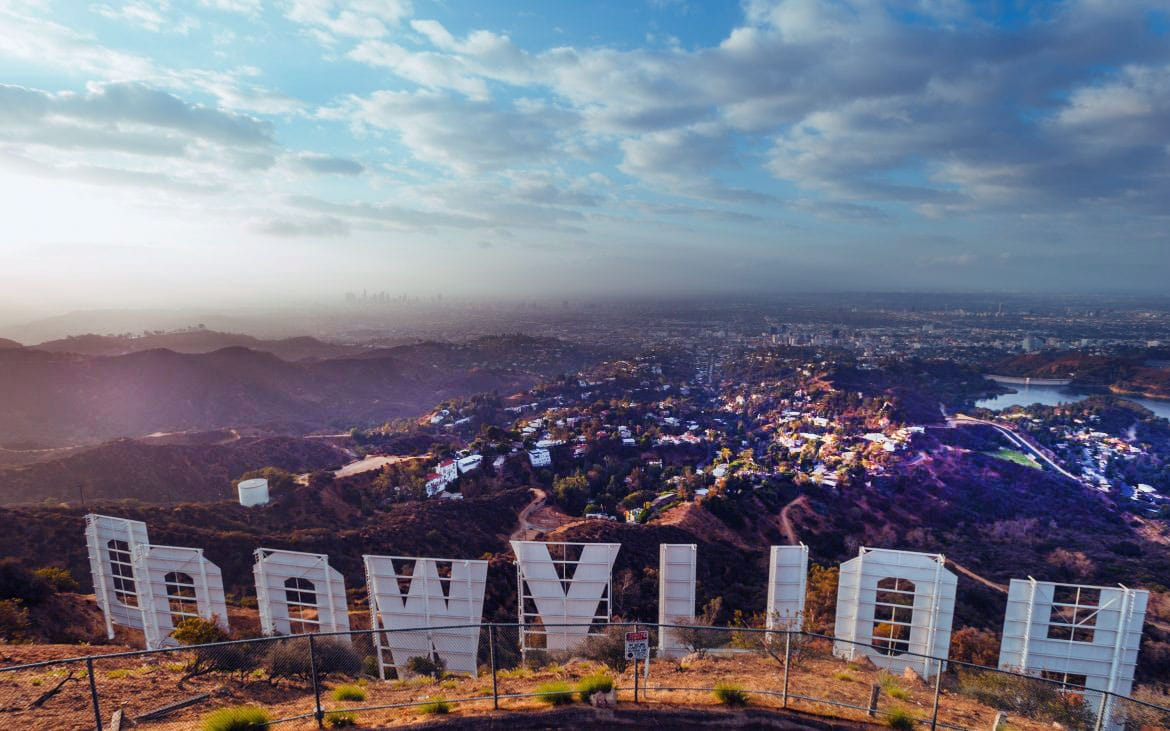 """View of a sweeping city from behind """"Hollywood"""" sign"""