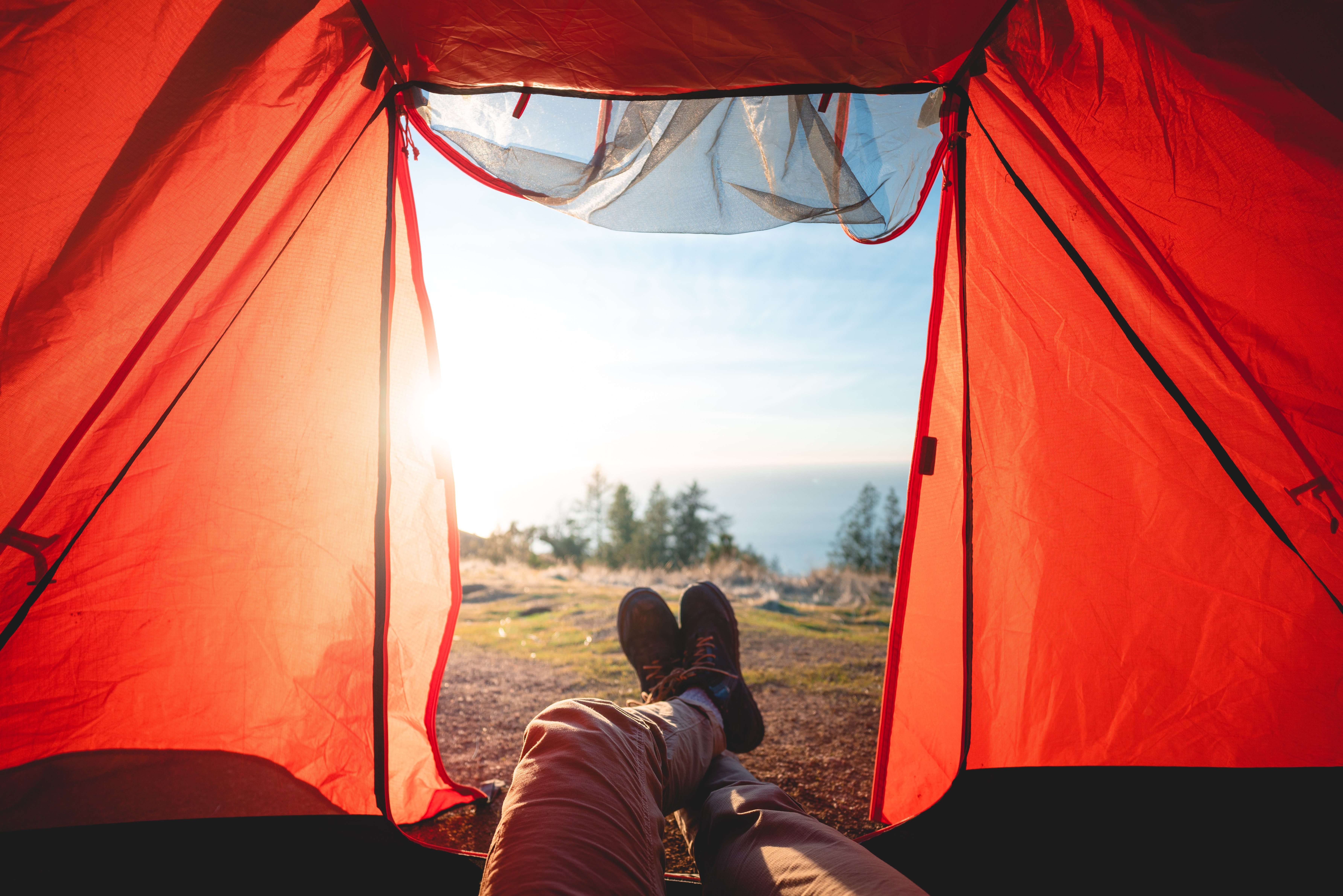 Man's legs hanging out of tent with lake view