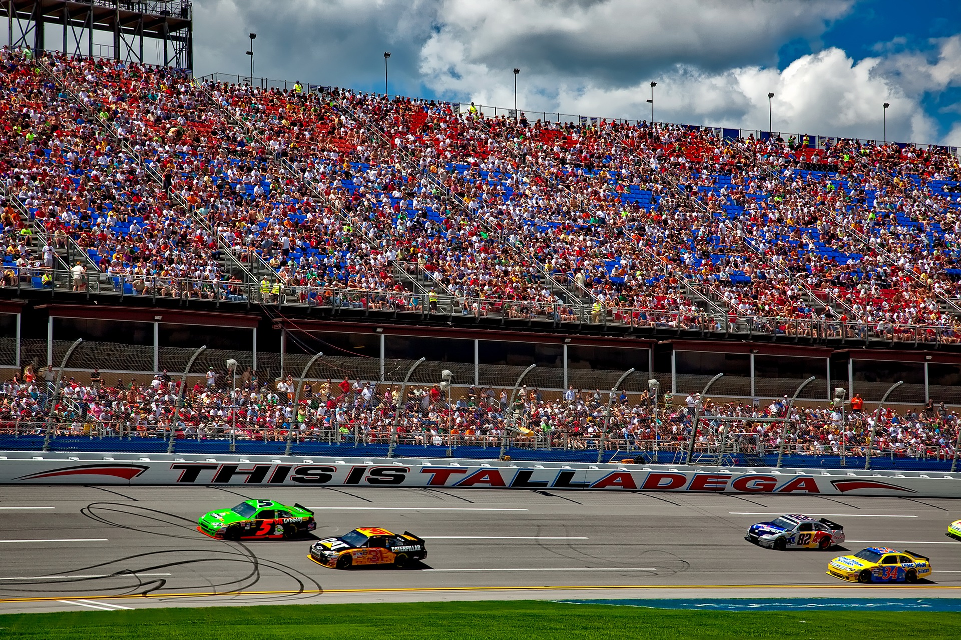 Colorful stock cars race around a track.