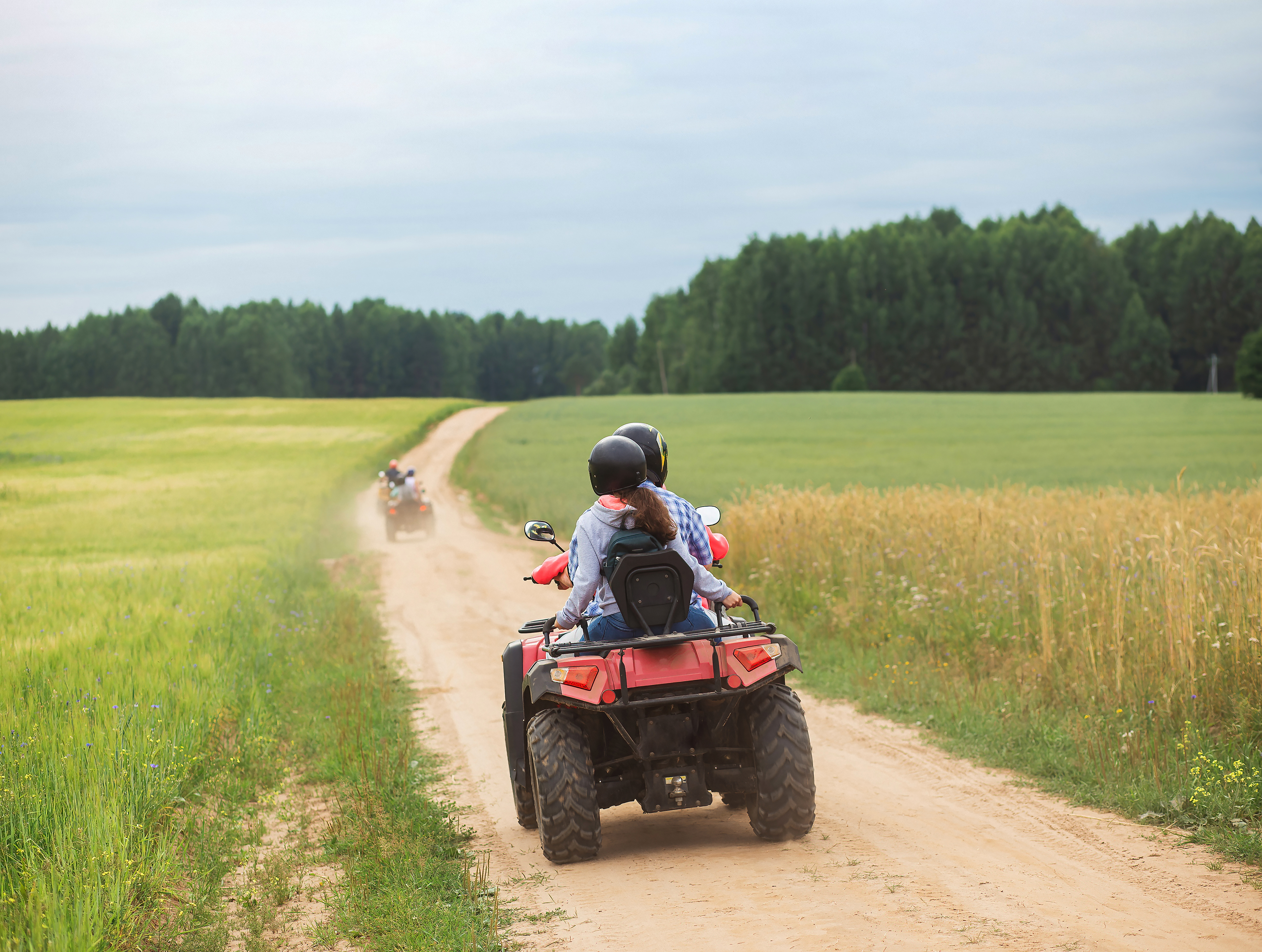 Good Sam Has Added 21 New Parks An ATV Quad sets out on a dusty trail toward a forest.