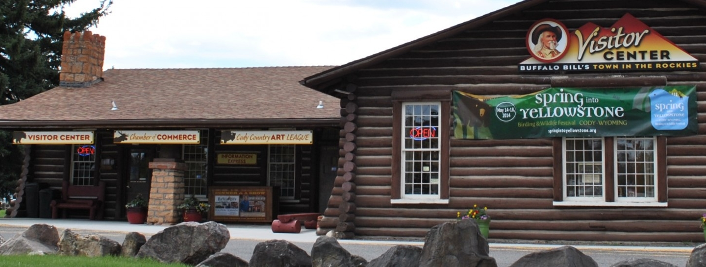 A visitor center with a log-cabin facade and likeness of Buffalo Bill on the side.