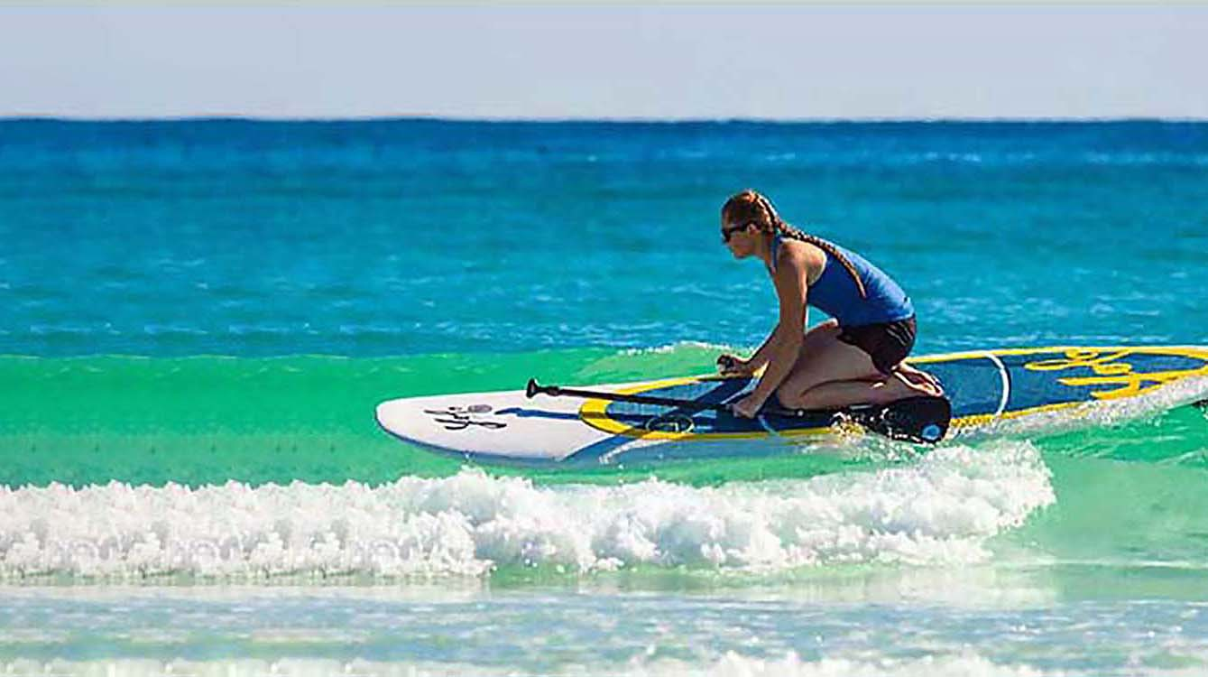 A young woman rides a wave on a paddleboard.