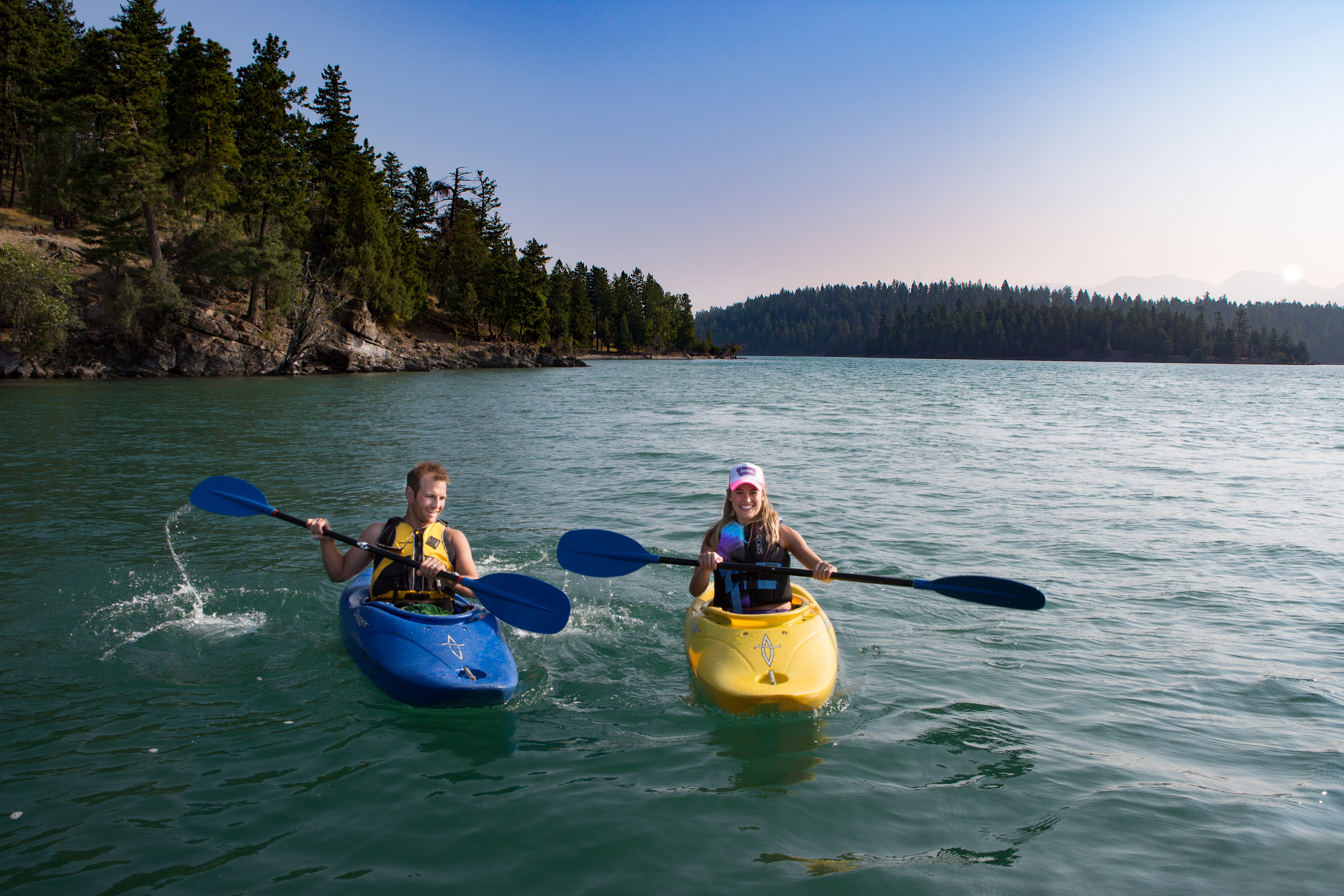 Two kayakers smile as they paddle a lake fringed in thick trees.