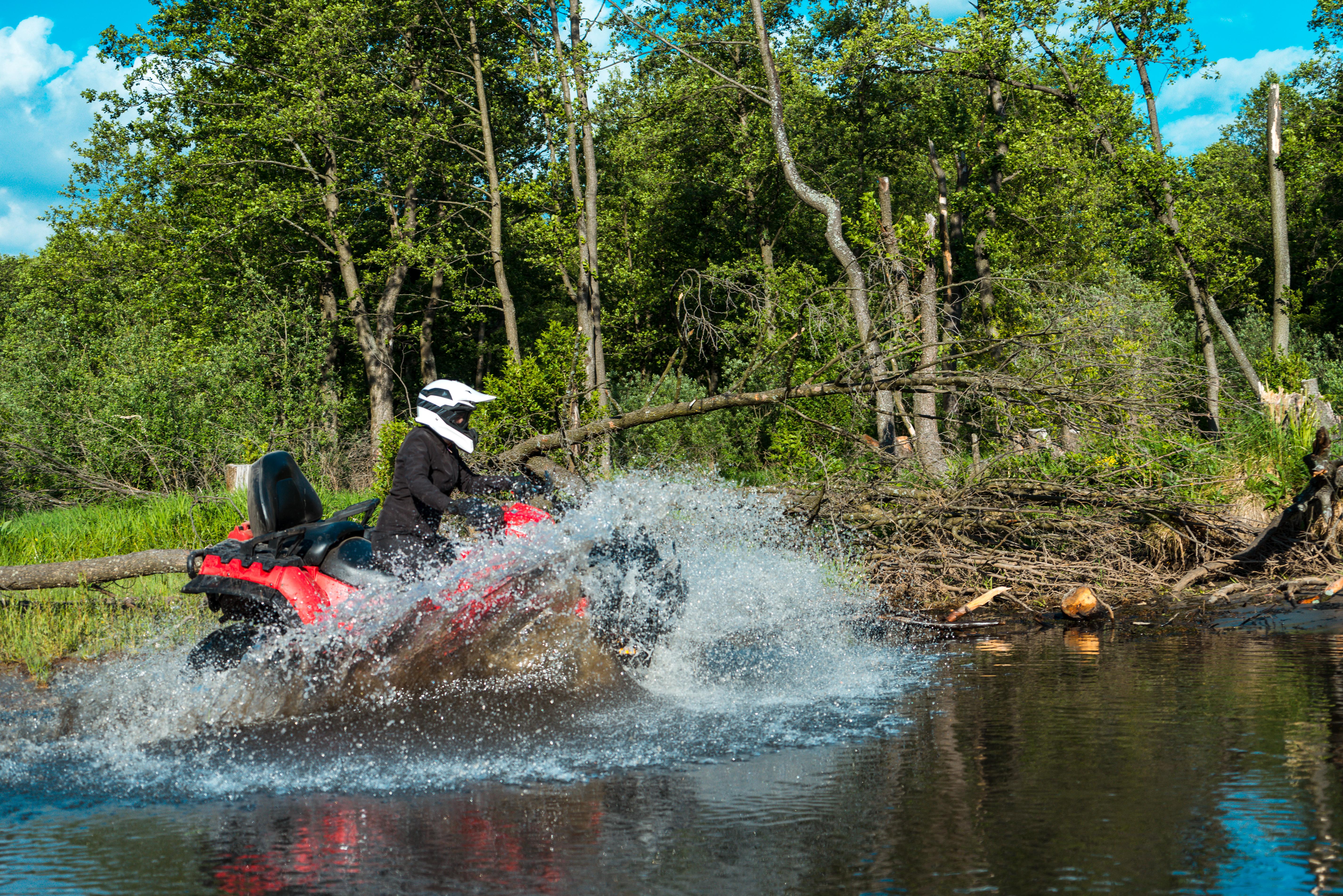 ATV rider fords a stream.