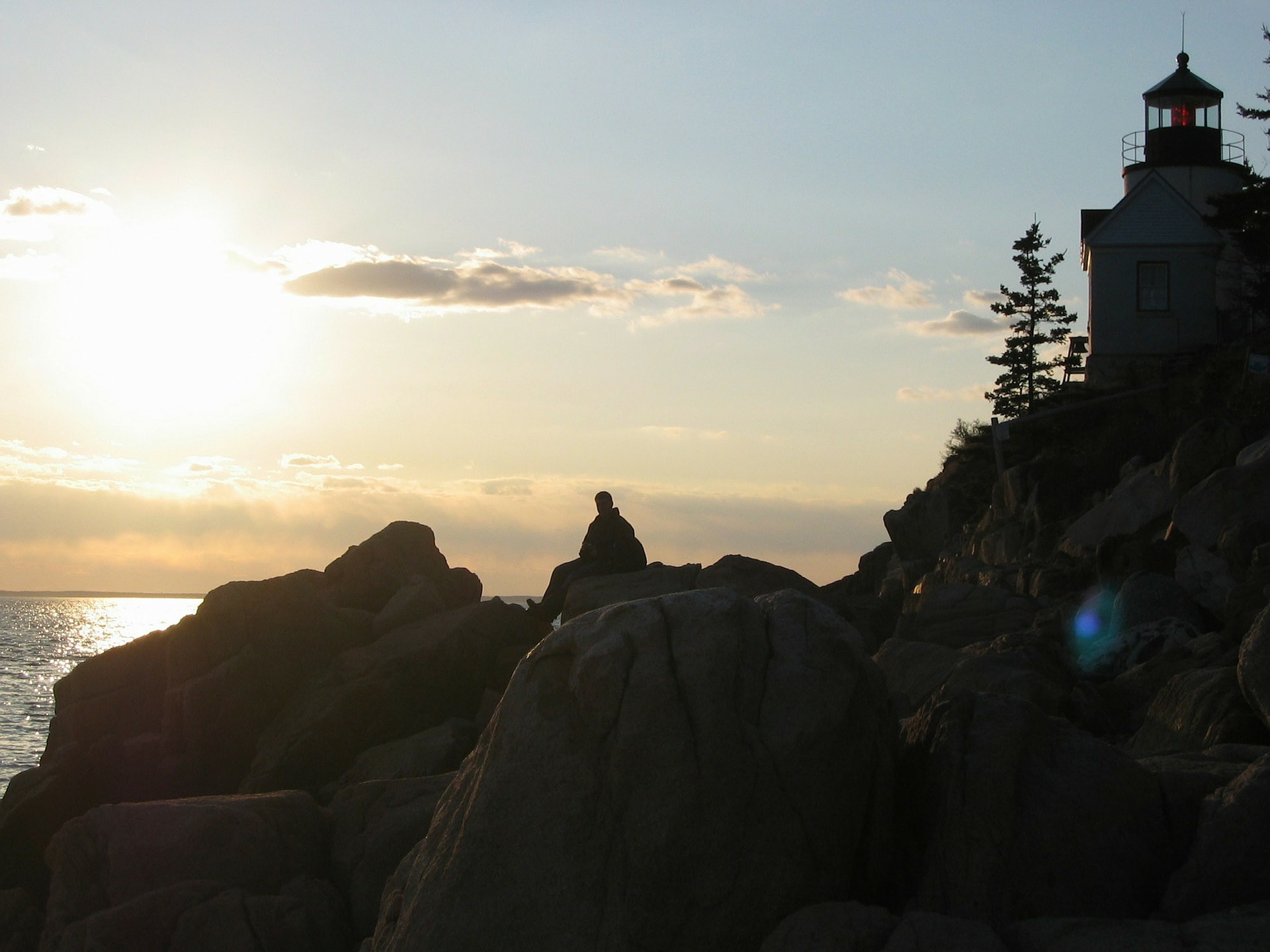Silhouette of a lighthouse at sunrise in Maine.