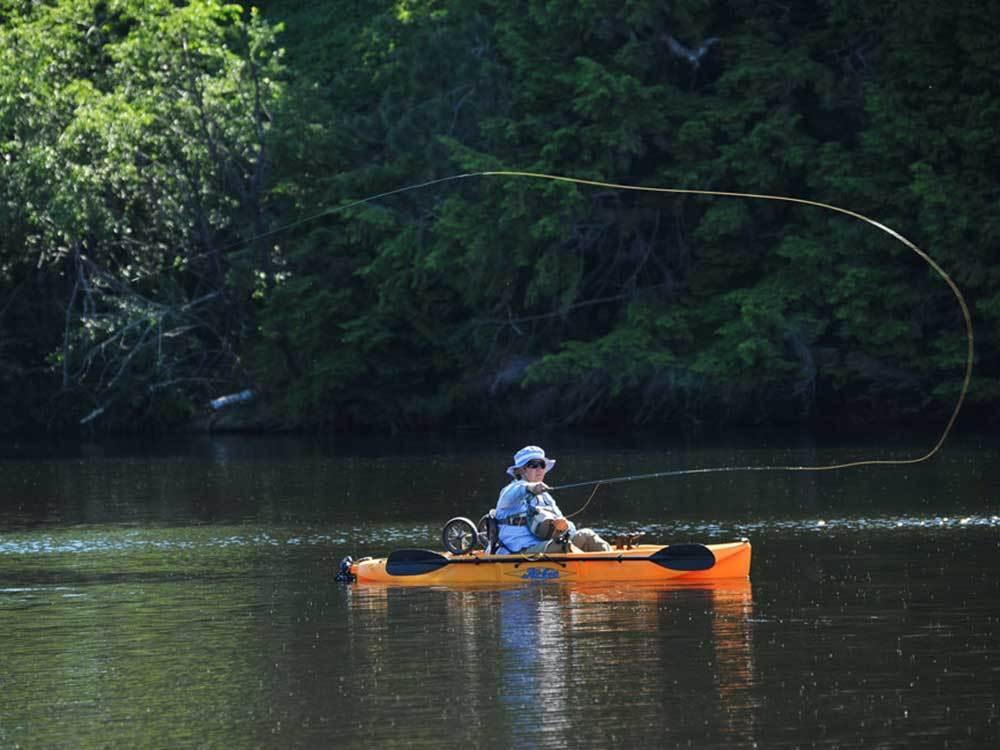 A camper sitting in an orange kayak casts a line on a placid lake.