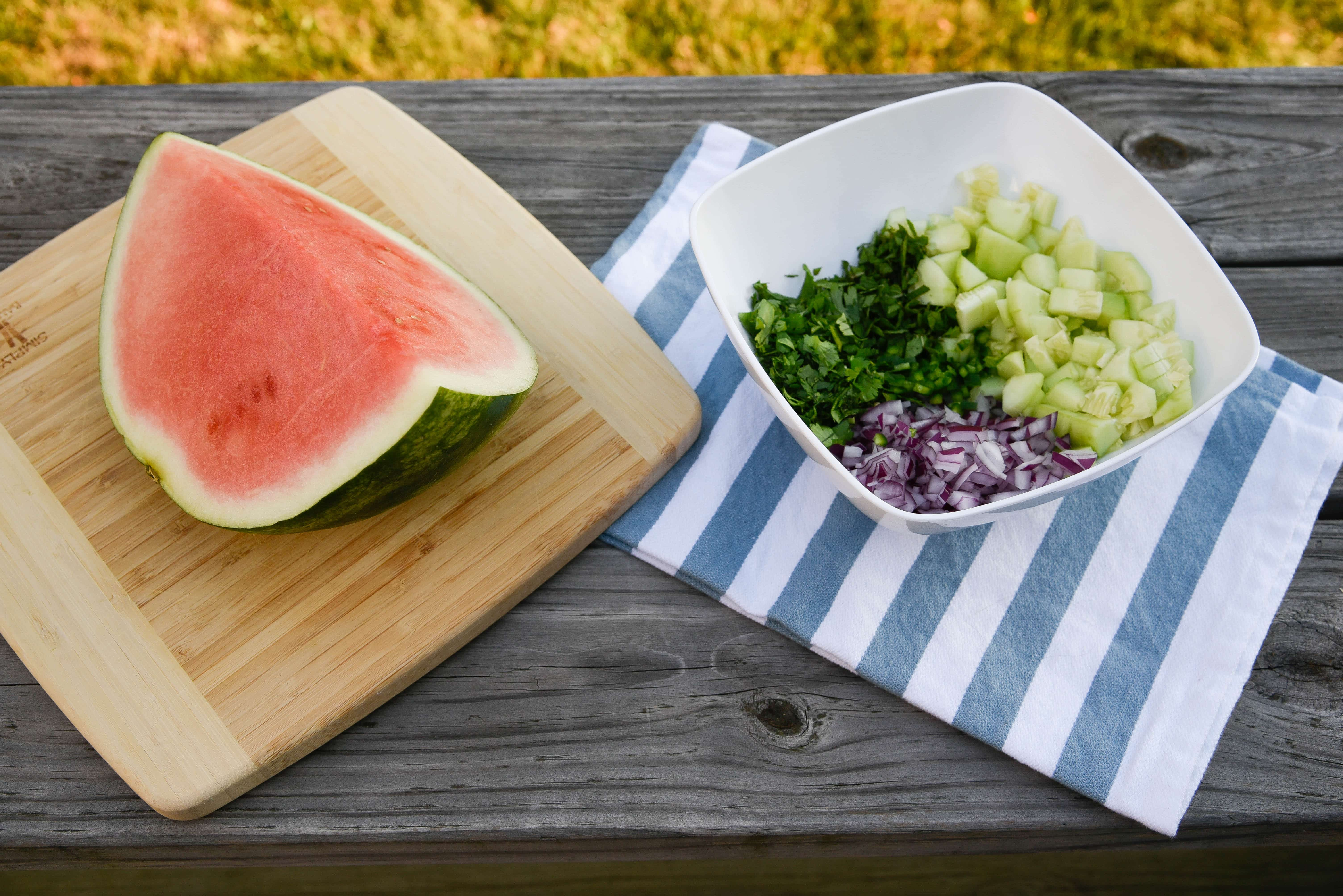 Watermelon quarter with a bowl fo salsa ingredients.