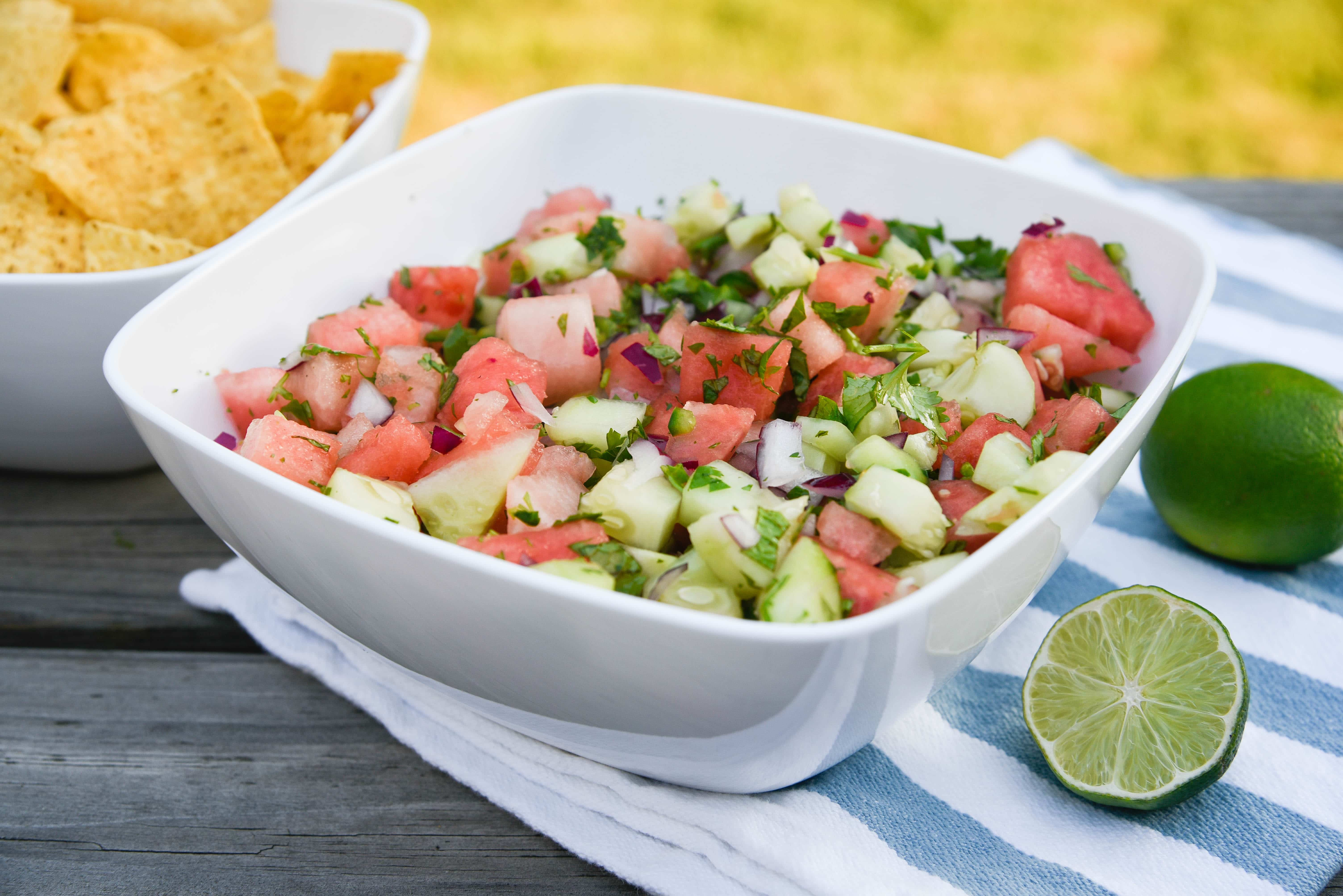 Bowl of watermelon salsa with chips in background.