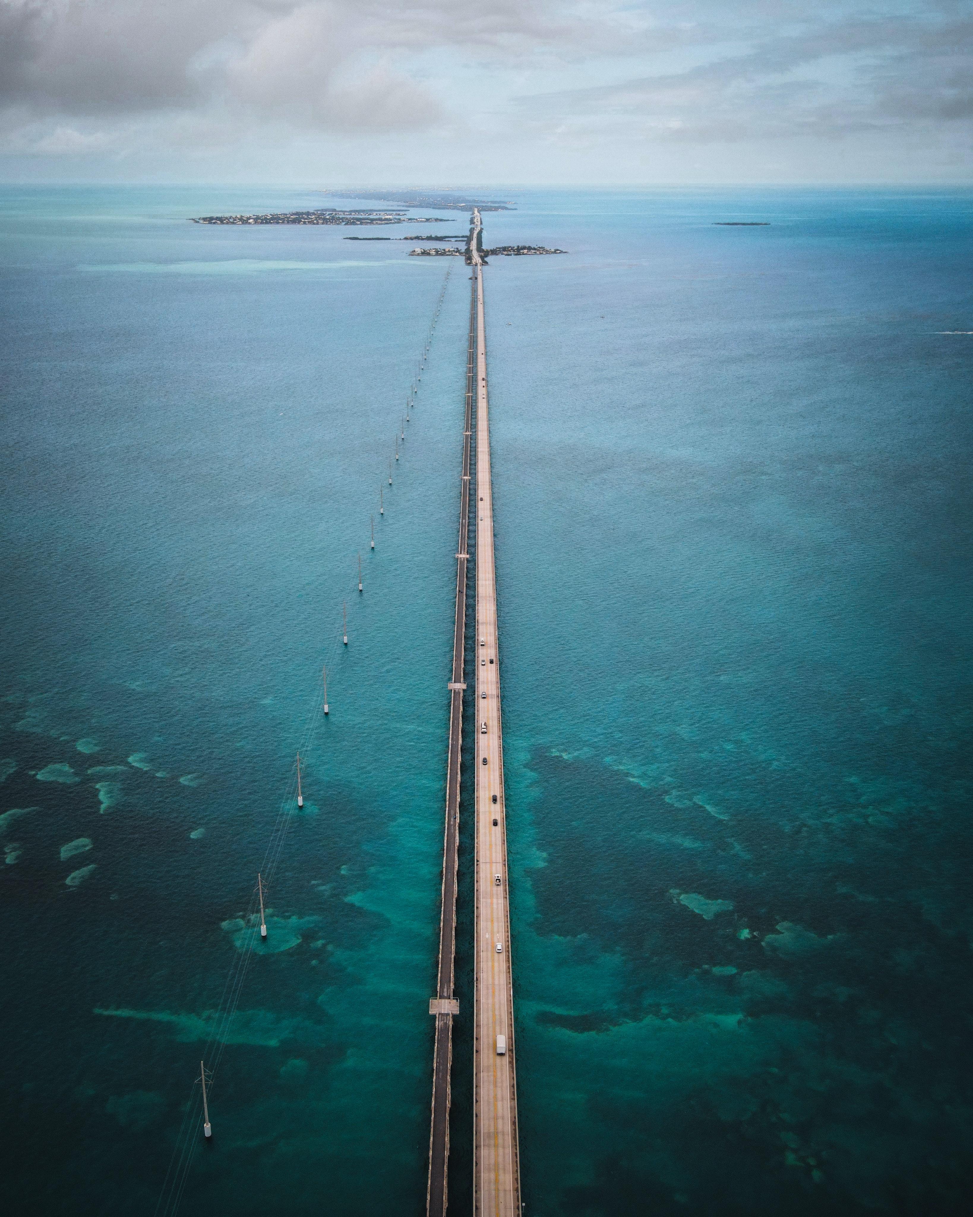 A bridge stretches across a vast expanse of dark turquoise ocean.