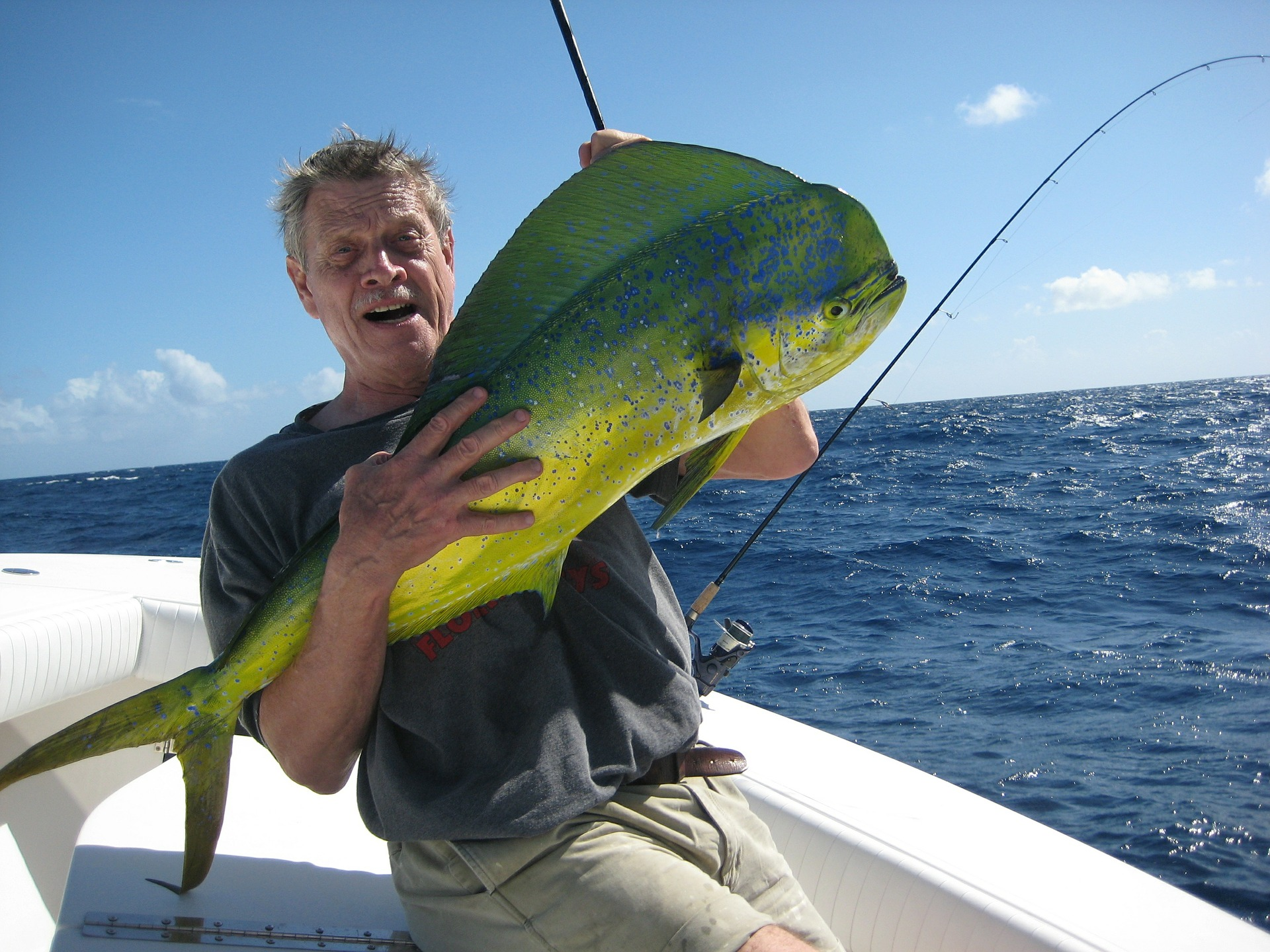Man holding a hefty green fish in his hand.