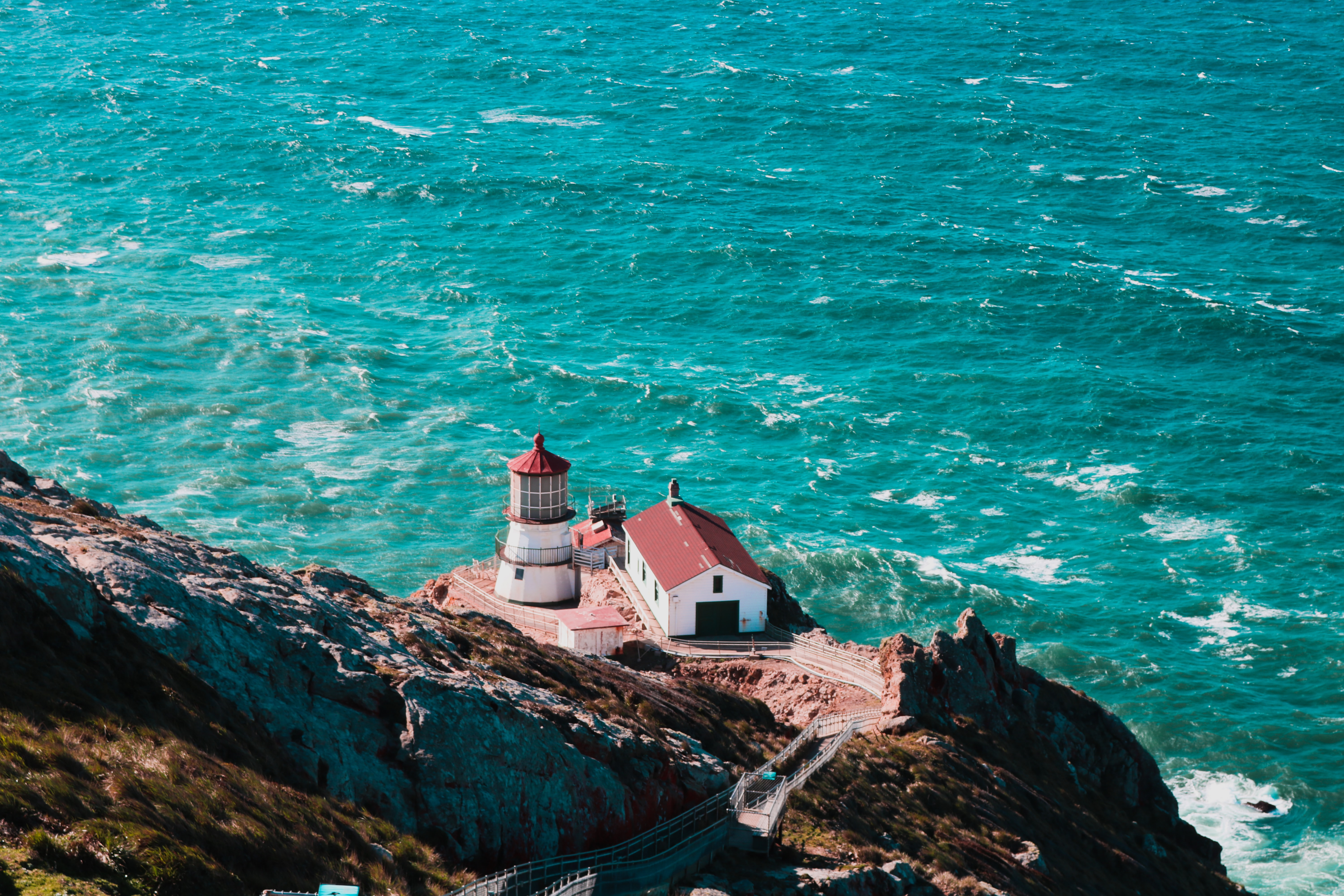 Lighthouse overlooking a turquoise ocean.