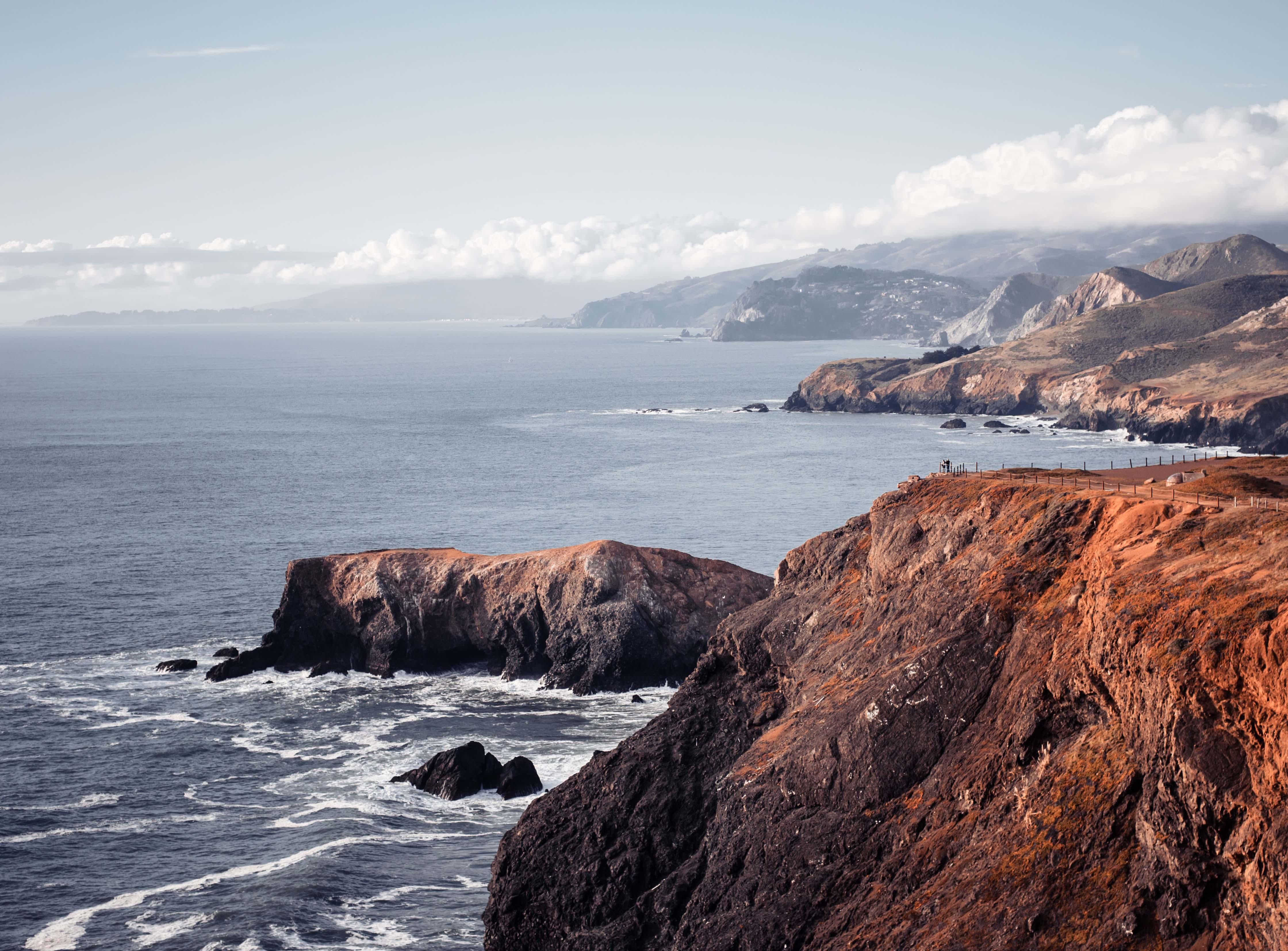 Crimson cliffs against turbulent ocean.
