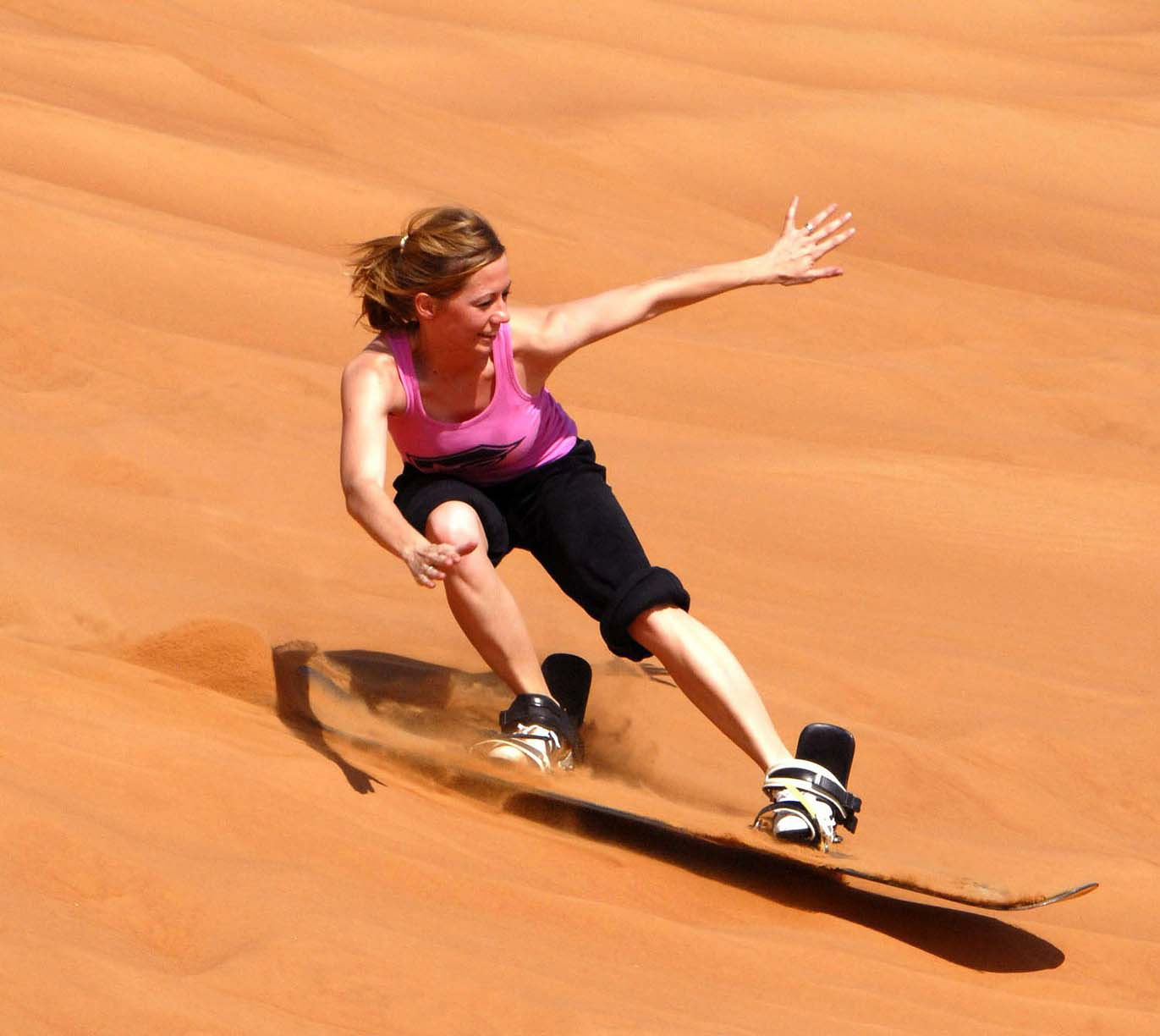 Woman rides a board down a sandy slope.
