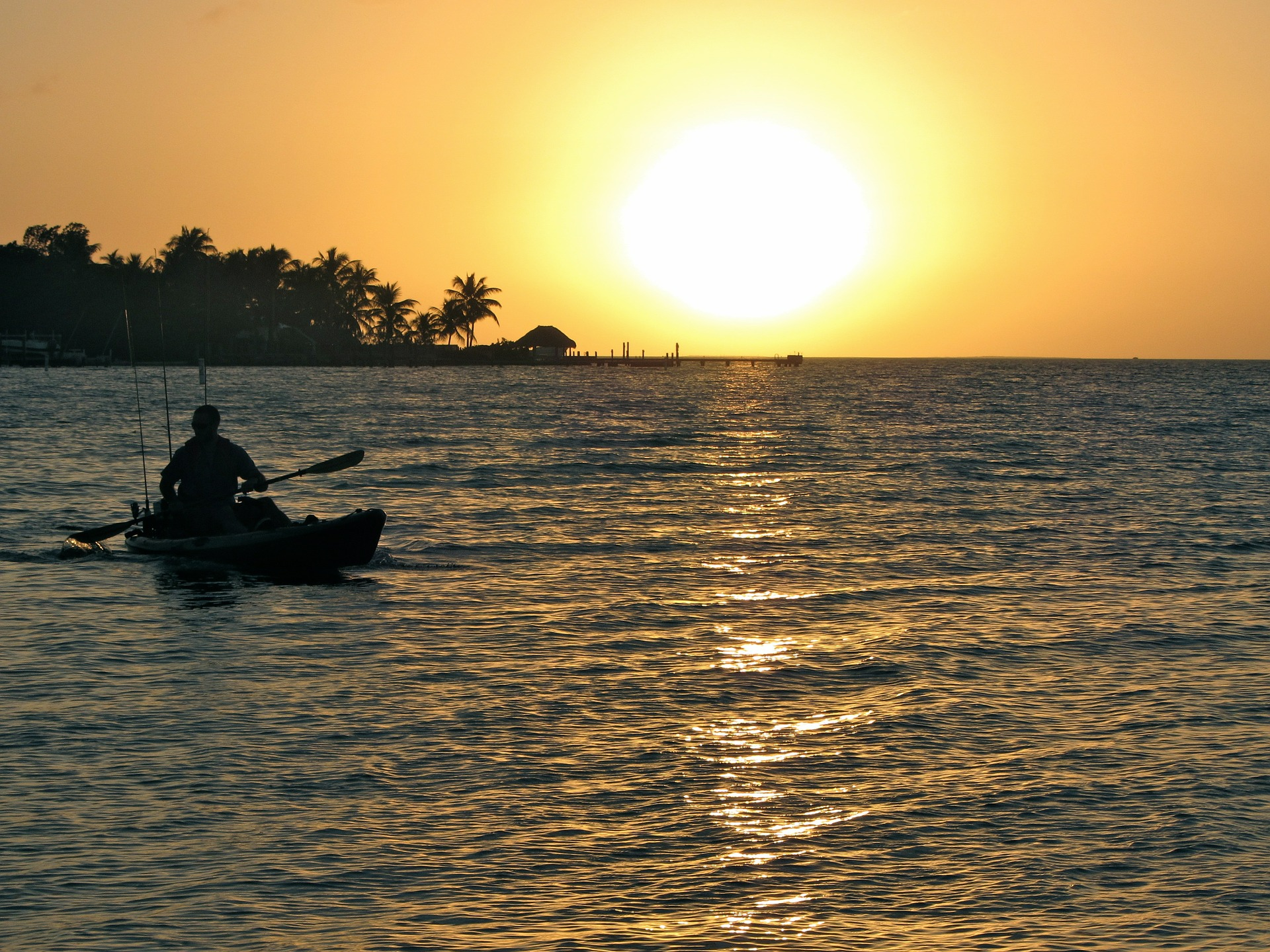 A kayaker paddles across the ocean during sunset.