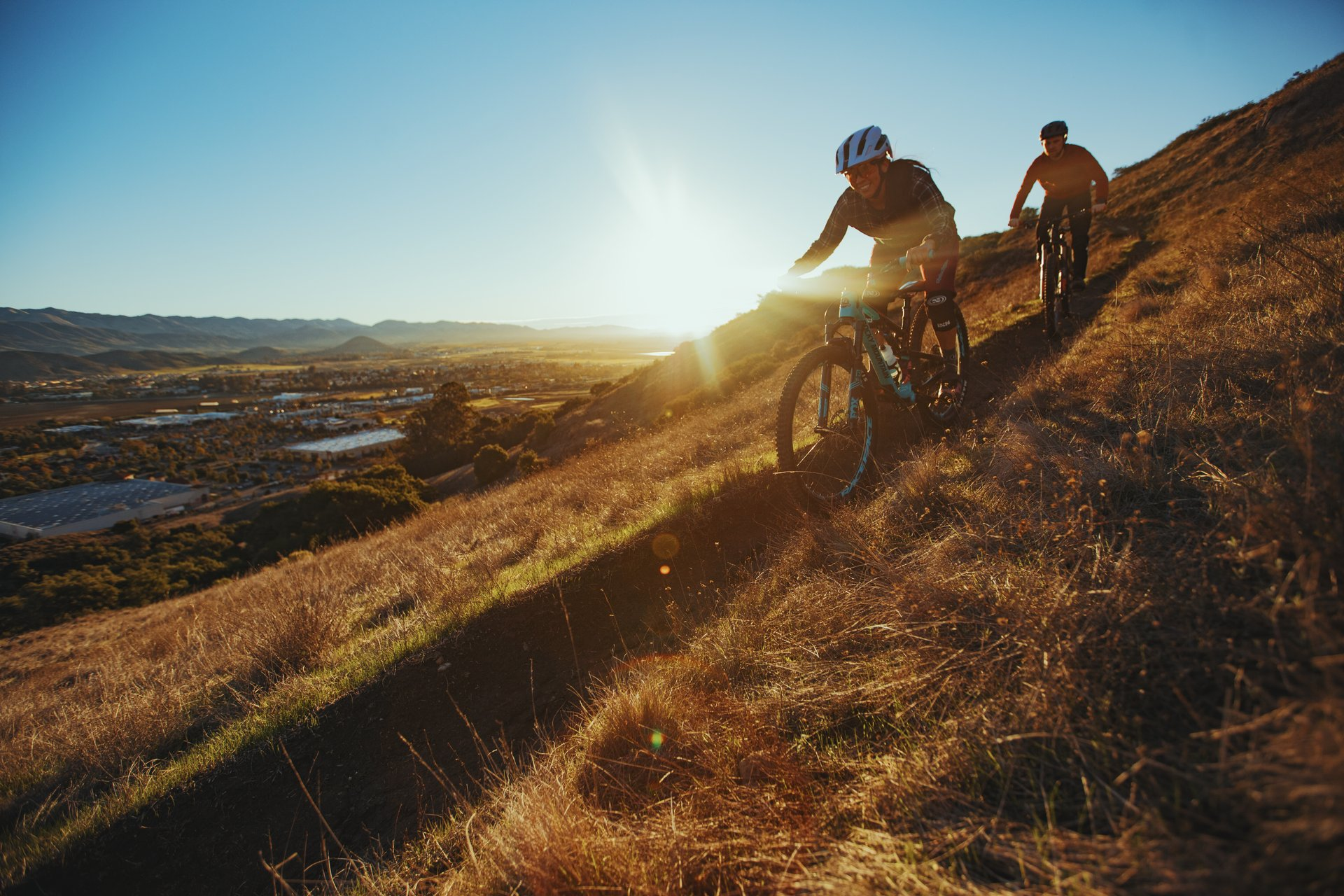 Cyclists coast down a steep trail.