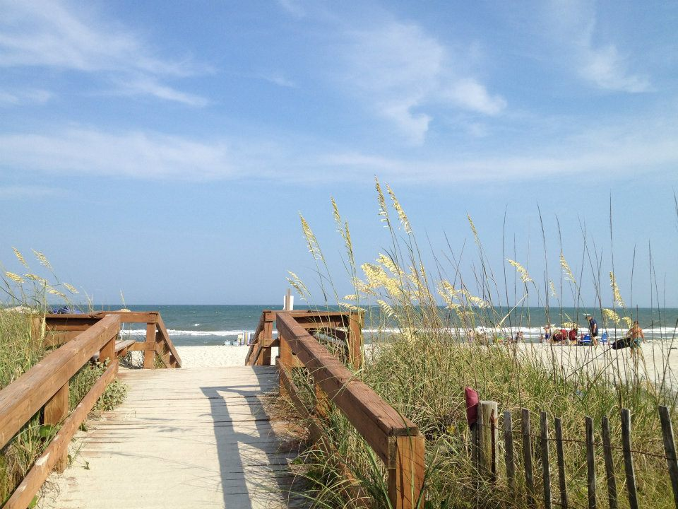 A wooden walkway leading to an unspoiled beach.