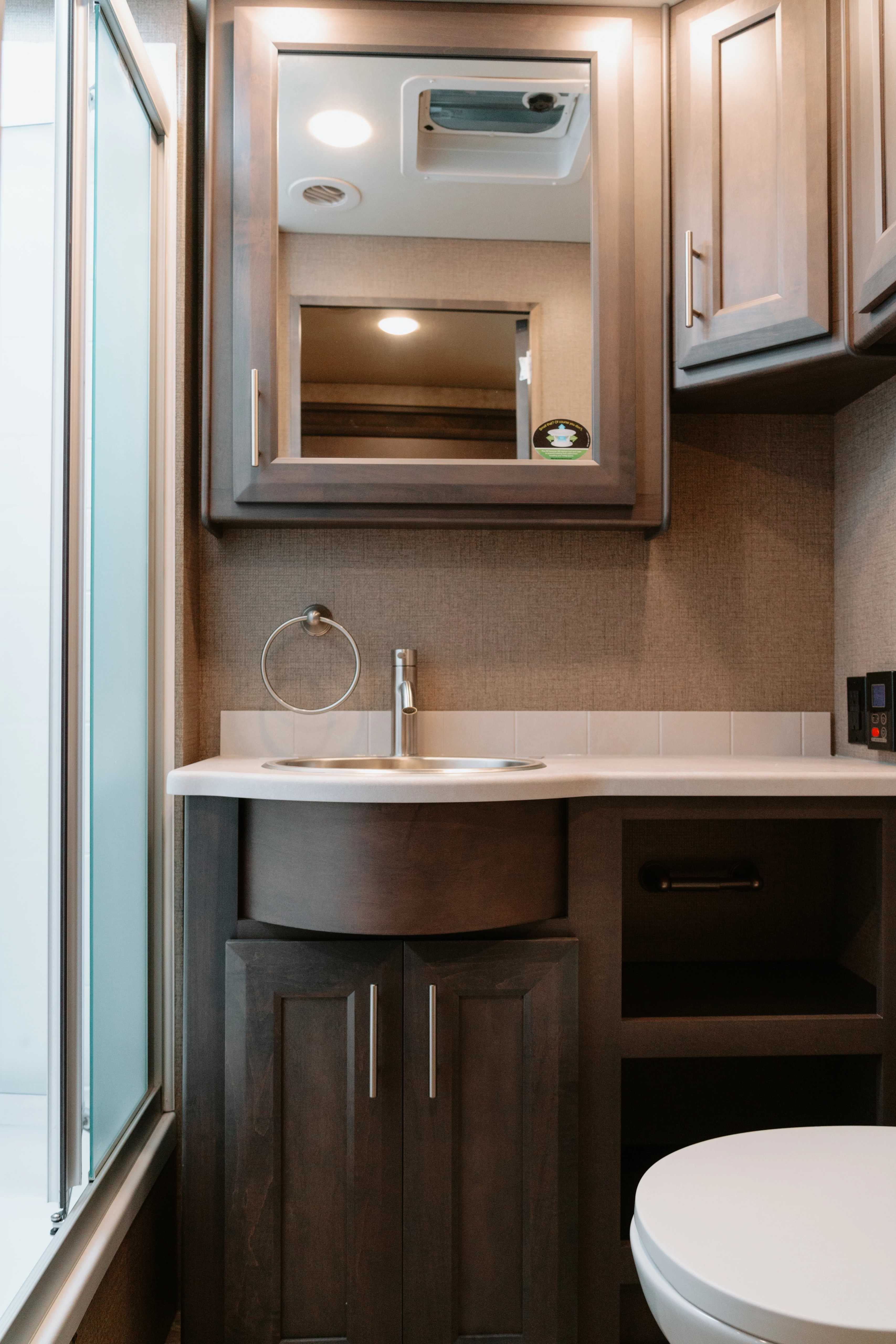 RV Bathroom interior with wood cabinetry and toilet