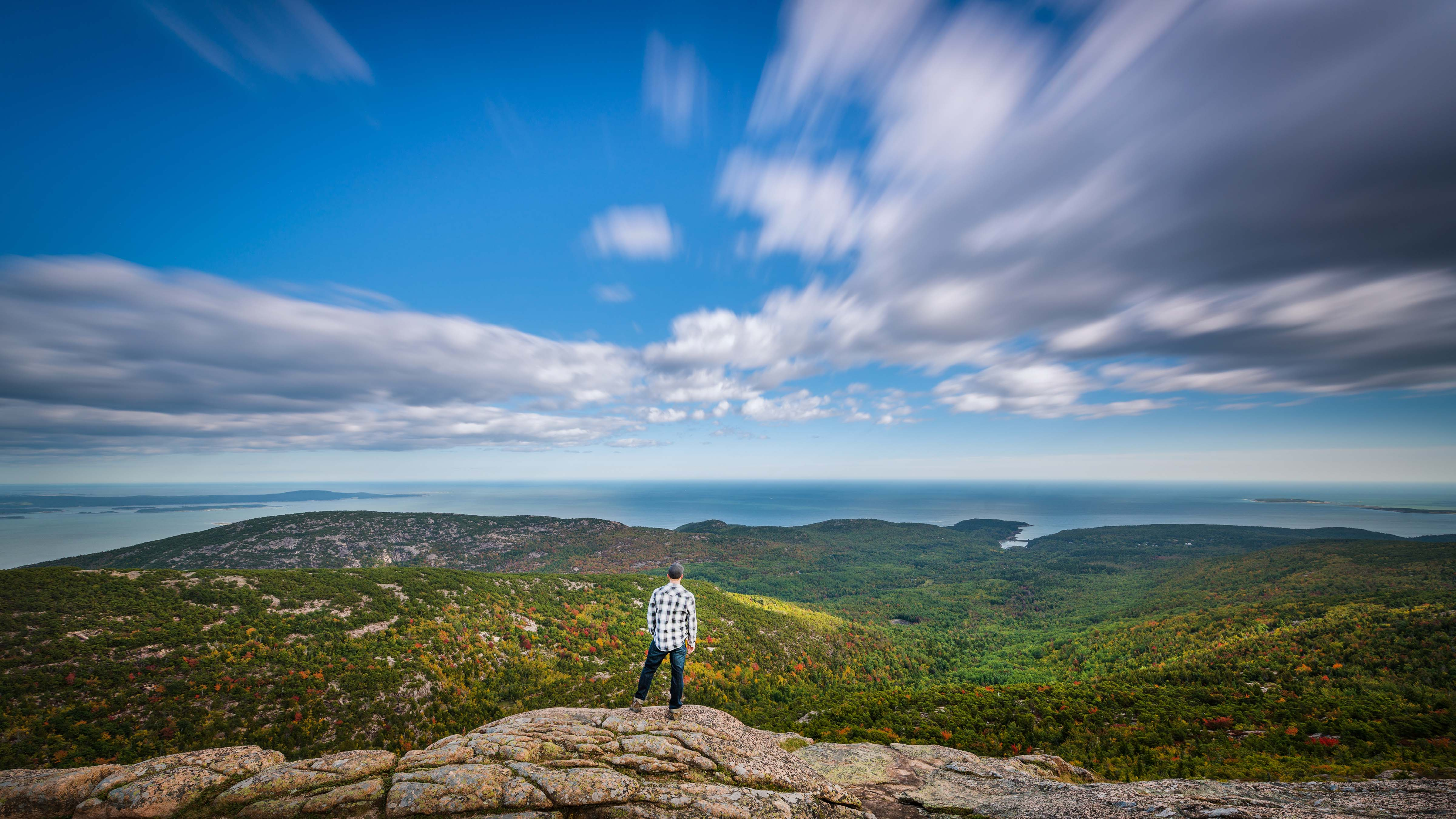 Coast of Maine — Man overlooks mountain vista as clouds race by.