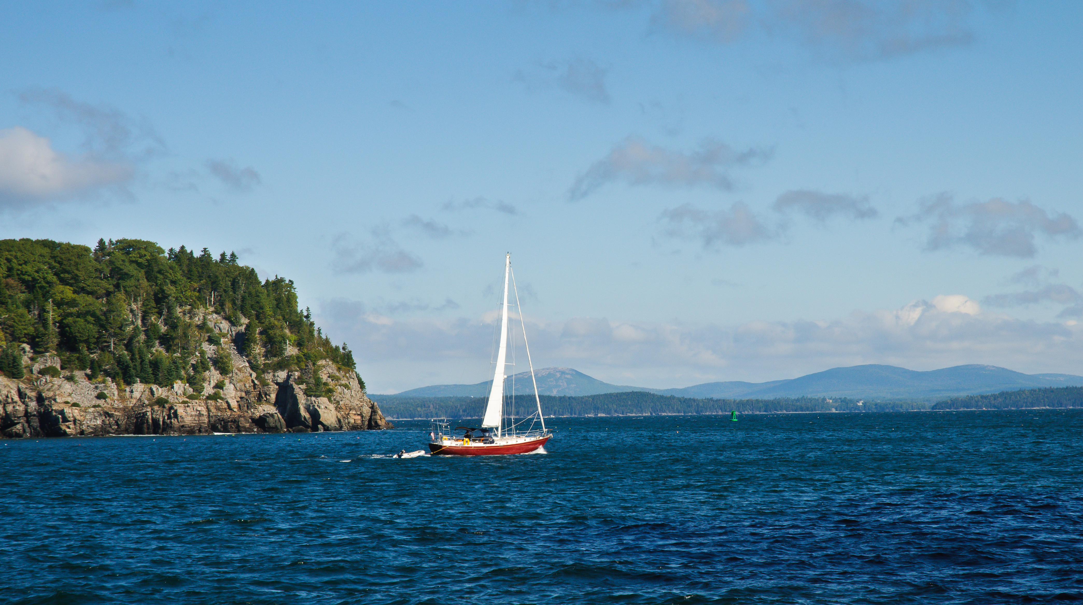 A lone sailboat sails out of a bay.