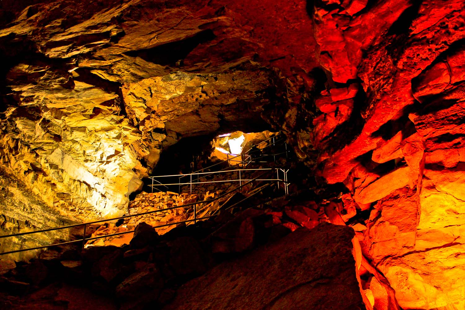 Mouth of a cave bathed in red light.