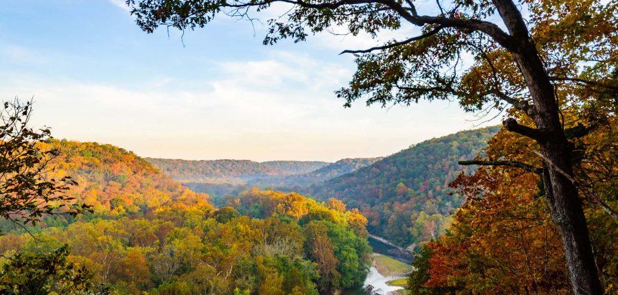 A river runs through a valley during fall colors.