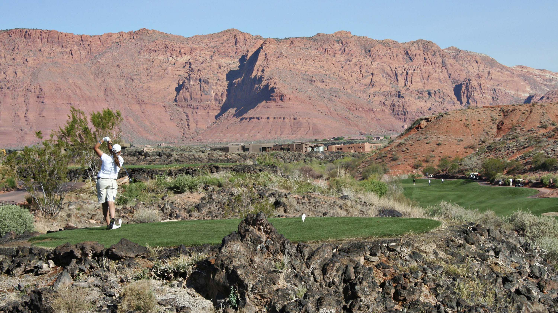 A woman swings a golf club in a desert environment.
