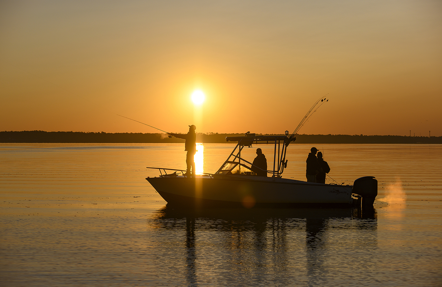 Anglers cast a line on a boat during sunset.