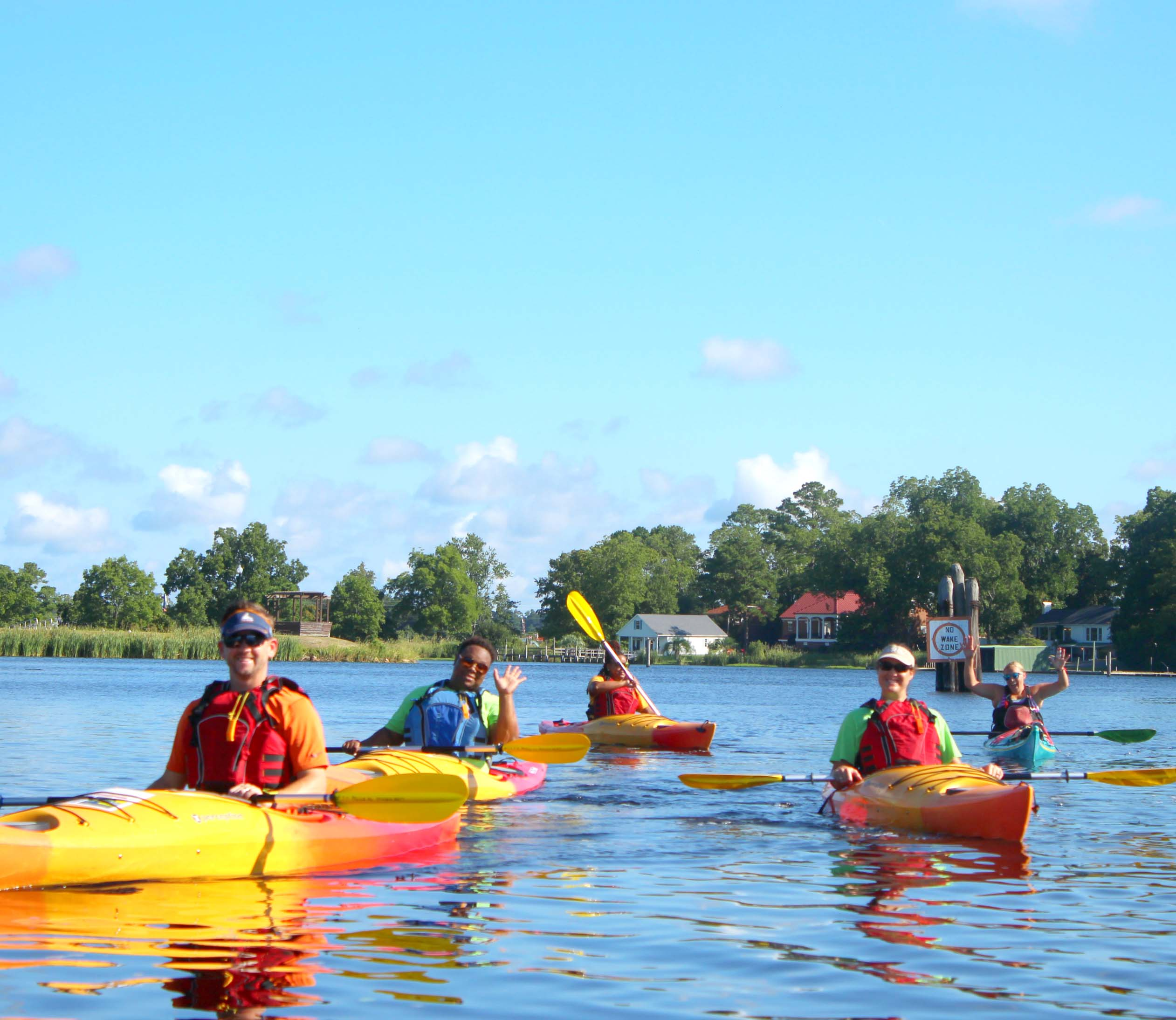 Five young kayakers paddle on a placid lake.