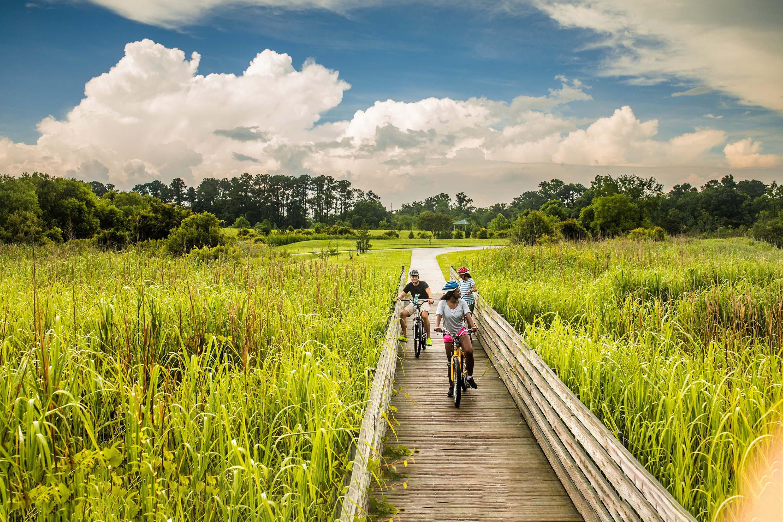 Three cyclists on a boardwalk that spans a vast grassy expanse.