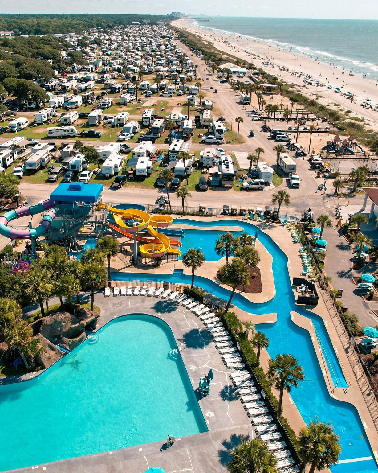 Aerial shot of RVs parked next to a beach shore with pool and lazy river.