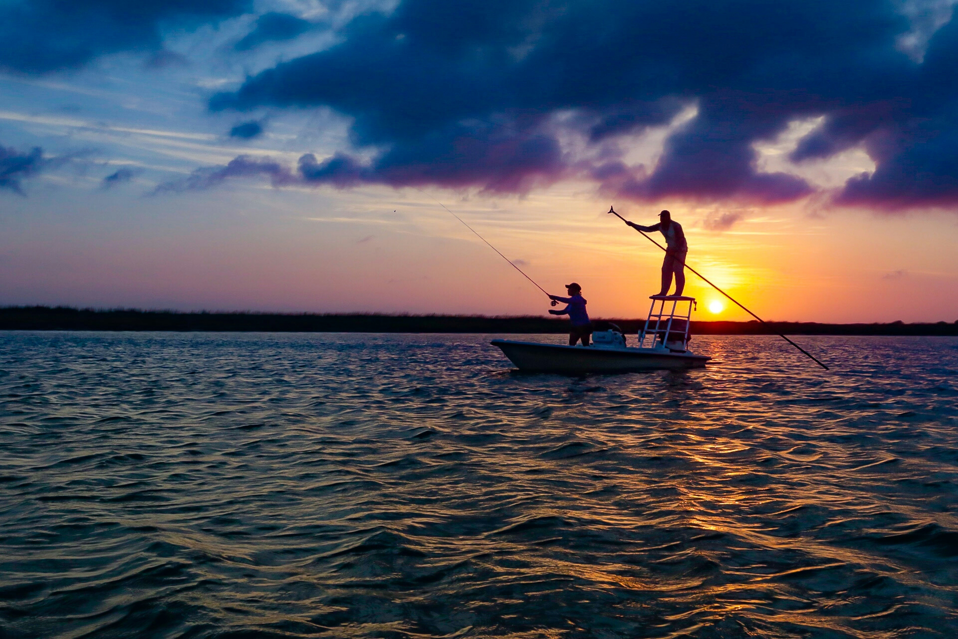 Anglers casting a line at sunset.