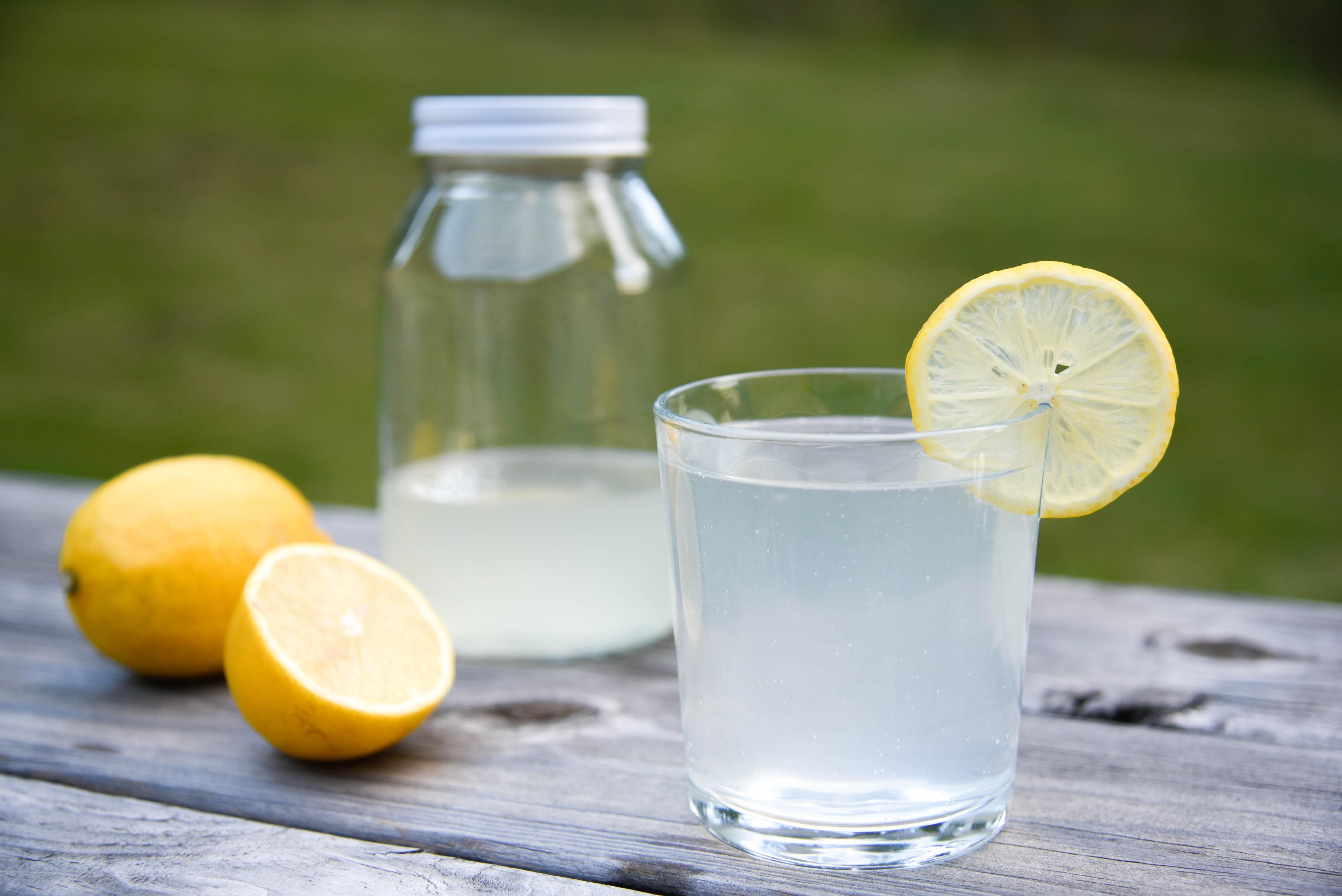 Glass with lemon slice and lemons.