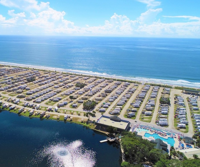 Aerial shot of RV park on an isthmus surrounded by ocean.