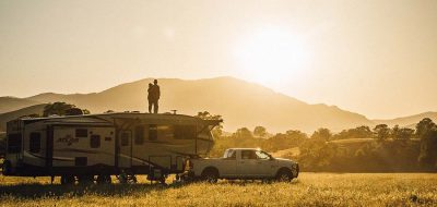 A young couple stands atop a fifth-wheel as the sunsets in the background.