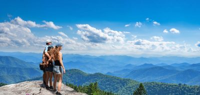 A family looks out at vista from mountain top.