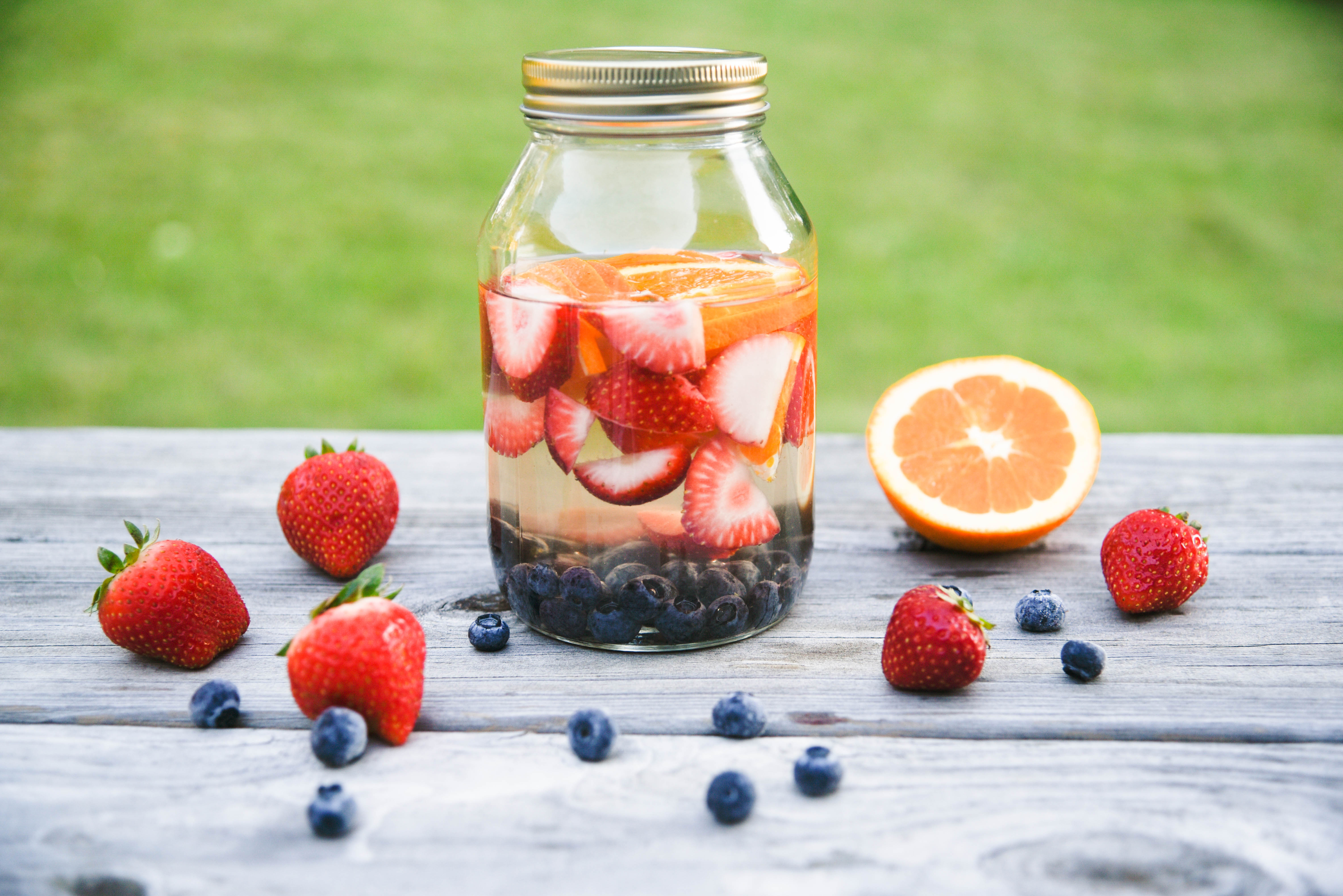 Jar with strawberries, oranges and blueberies