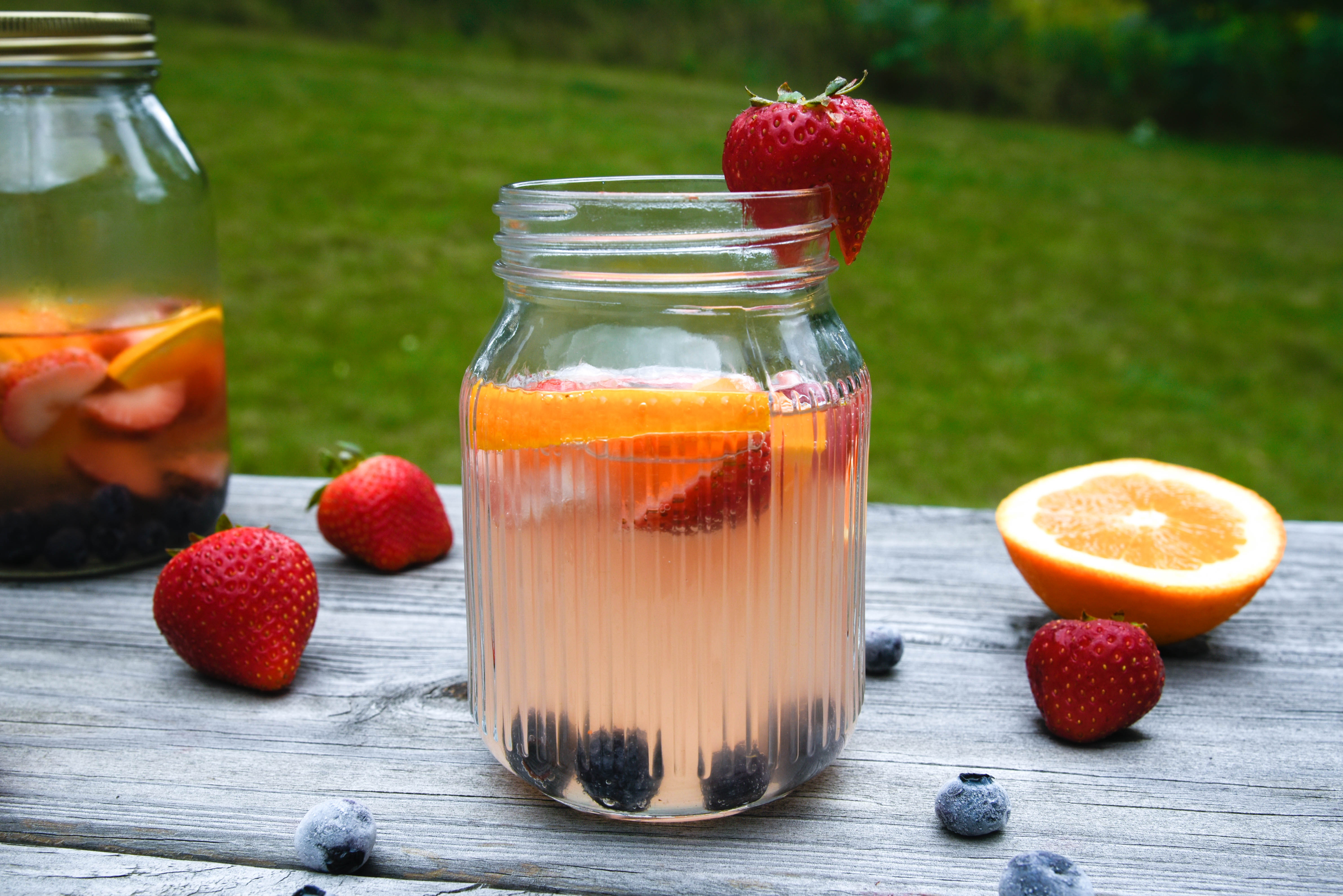 Jar with strawberry slice on rim surrounded by other fruit.