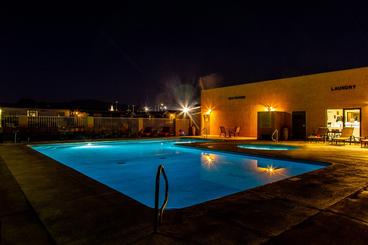 A pool illuminated by soft lighting during the evening.