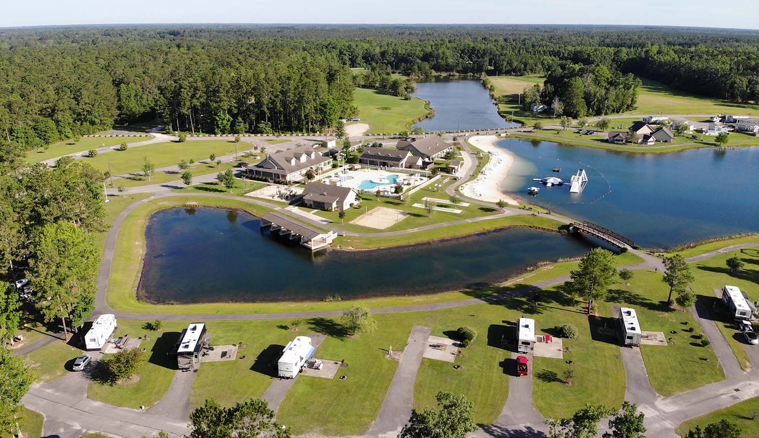 Aerial shot of RVs parked on green lawn around a pond area.