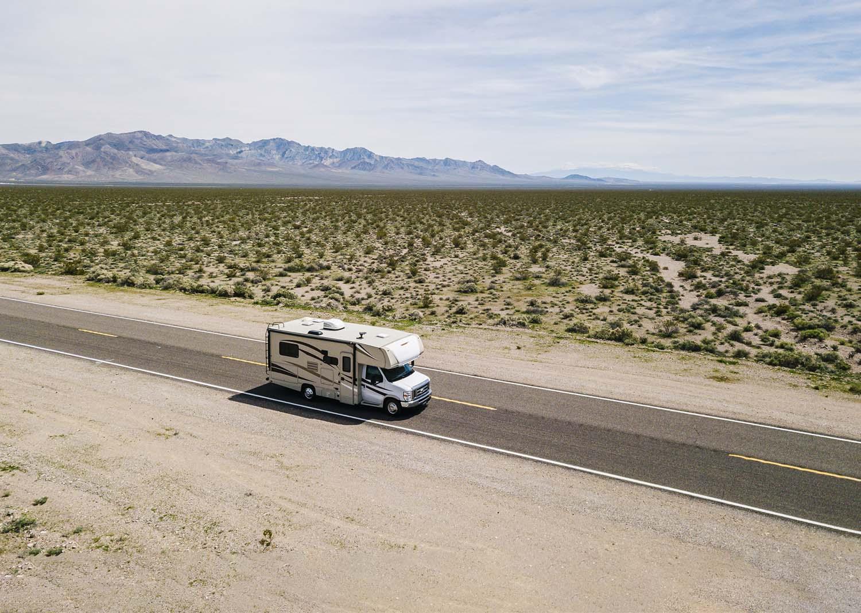 Class C motorhome driving down a desert highway.