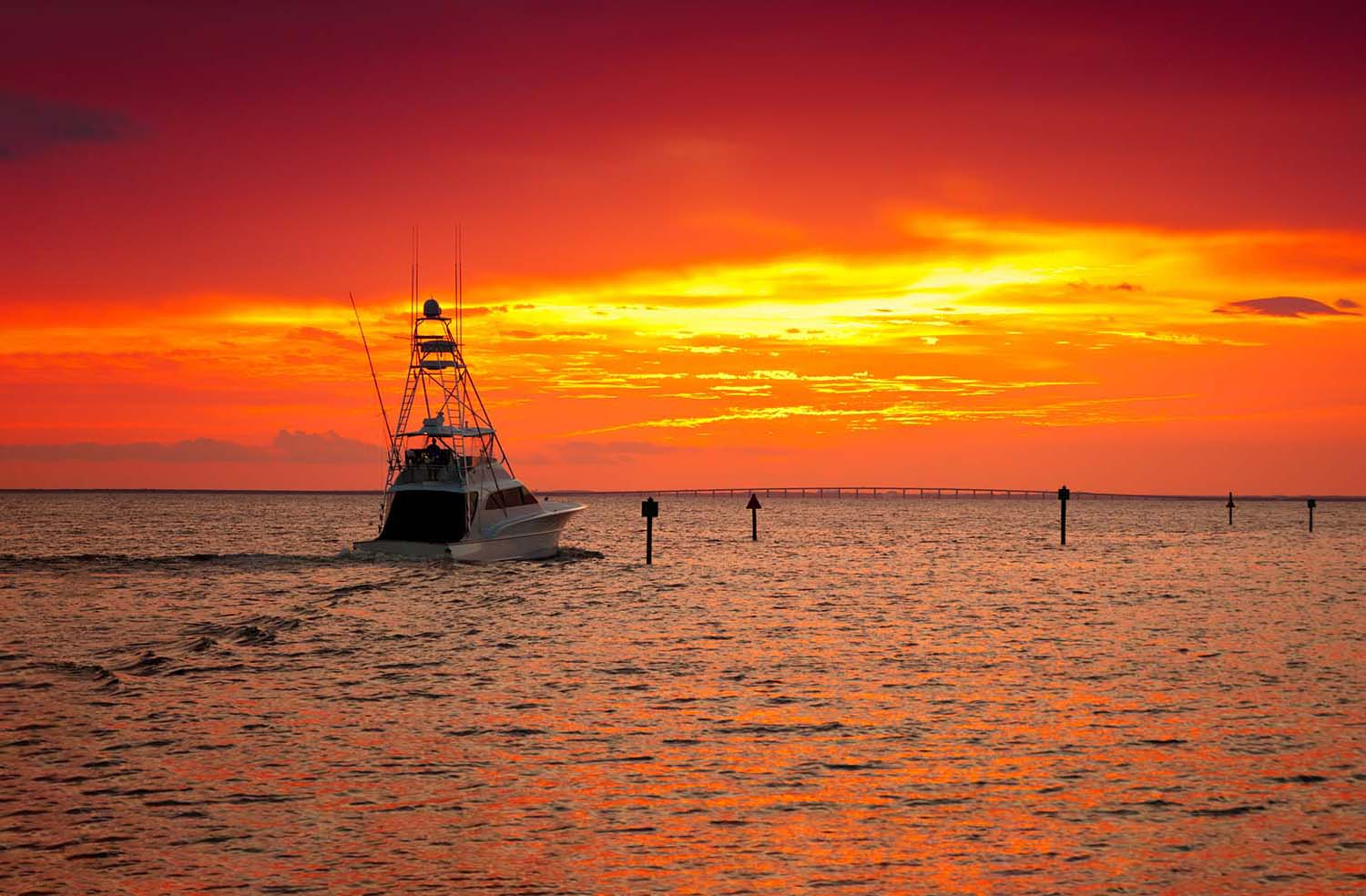 A fishing boat headed toward sunset under a red sky.