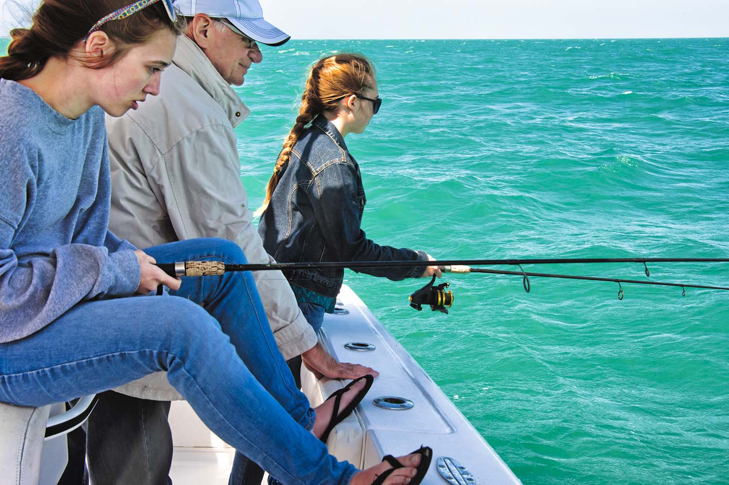 Grandfather, teaching his two teenager grandaughters his best tricks to catch some big fish.