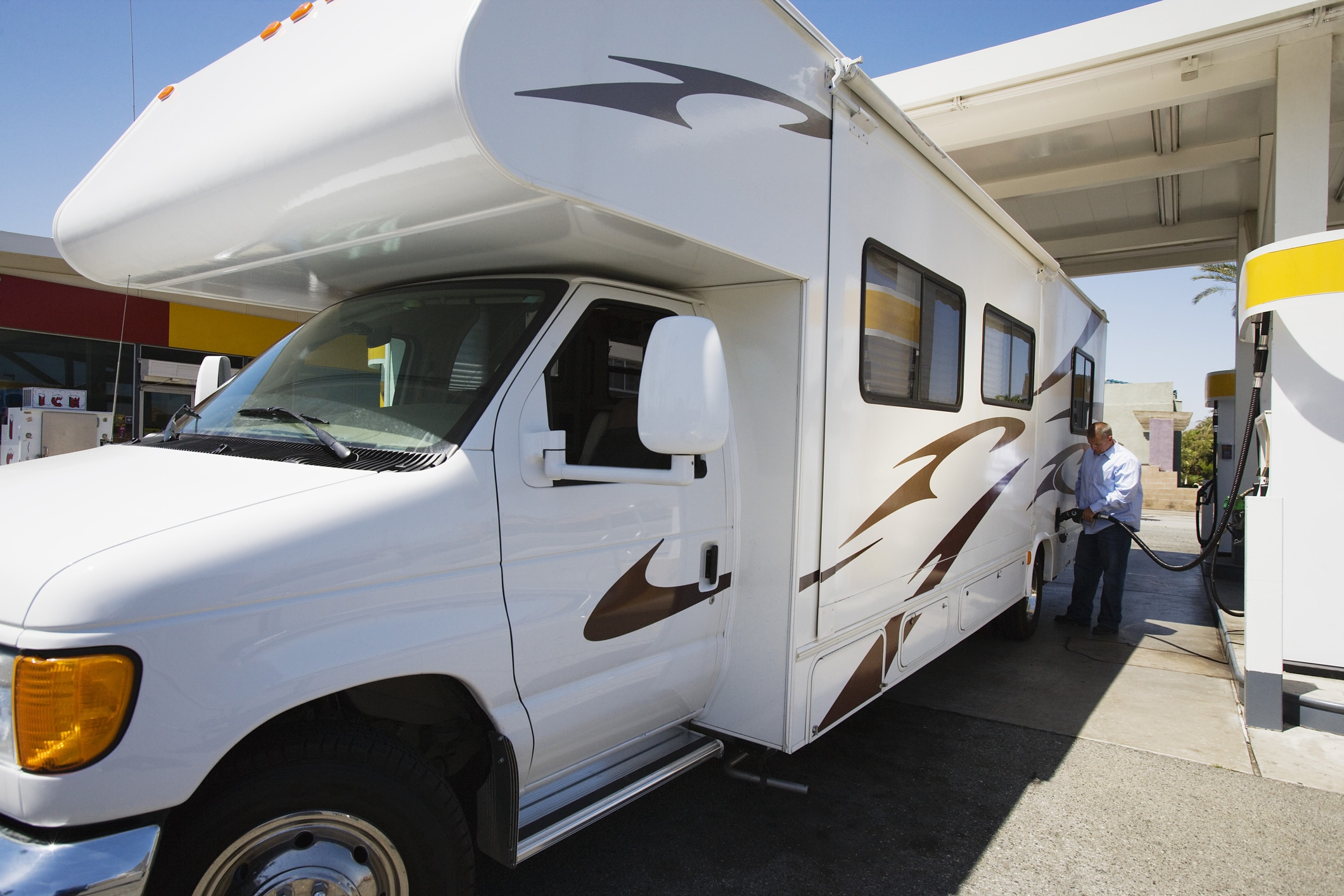Refueling a Class C motorhome at a service station.