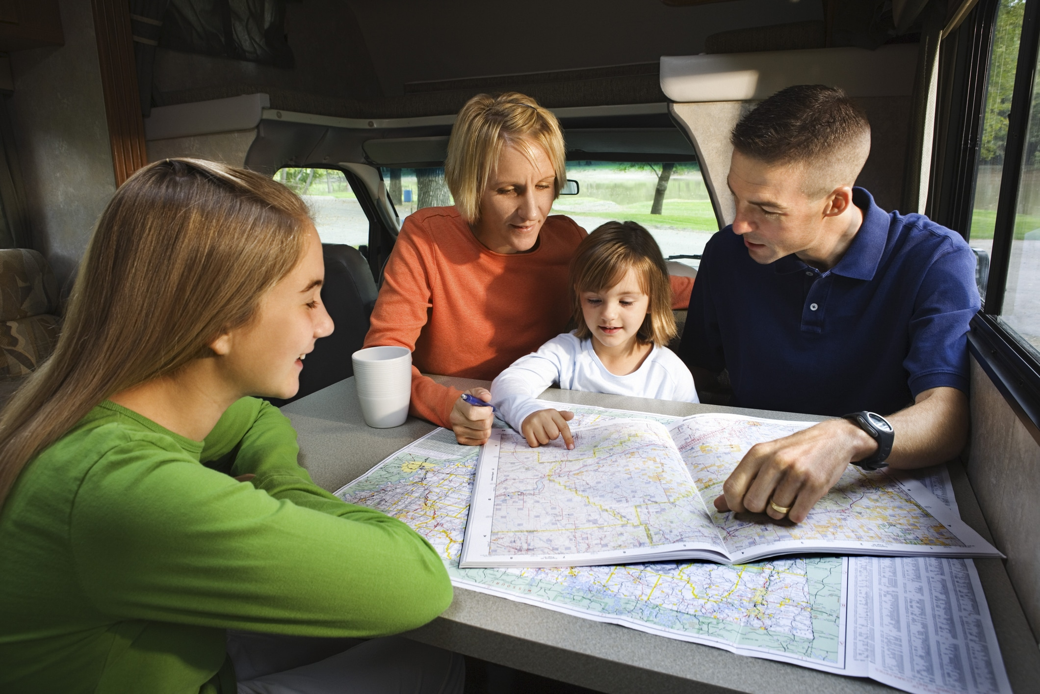 A family of four pours over a map in their RV.