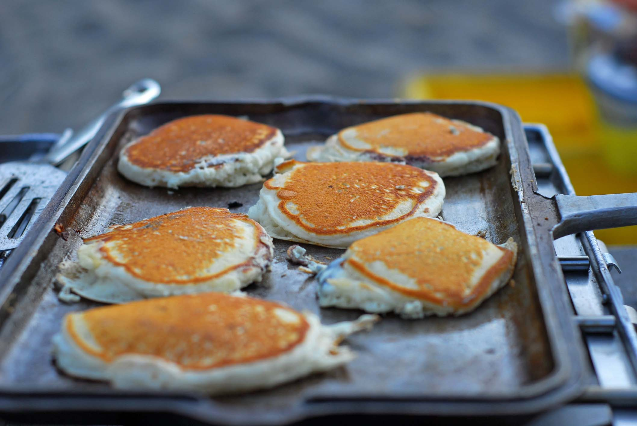 Six pancakes cooking on an outdoor grill.